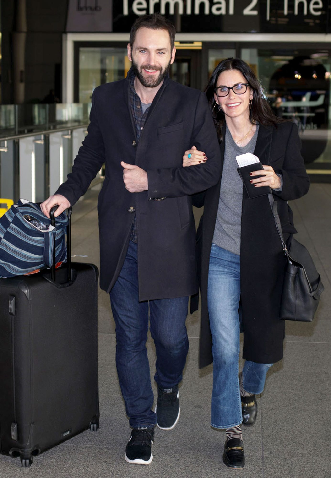 *EXCLUSIVE* Courteney Cox and Johnny McDaid are a cozy happy couple arriving at Heathrow Airport