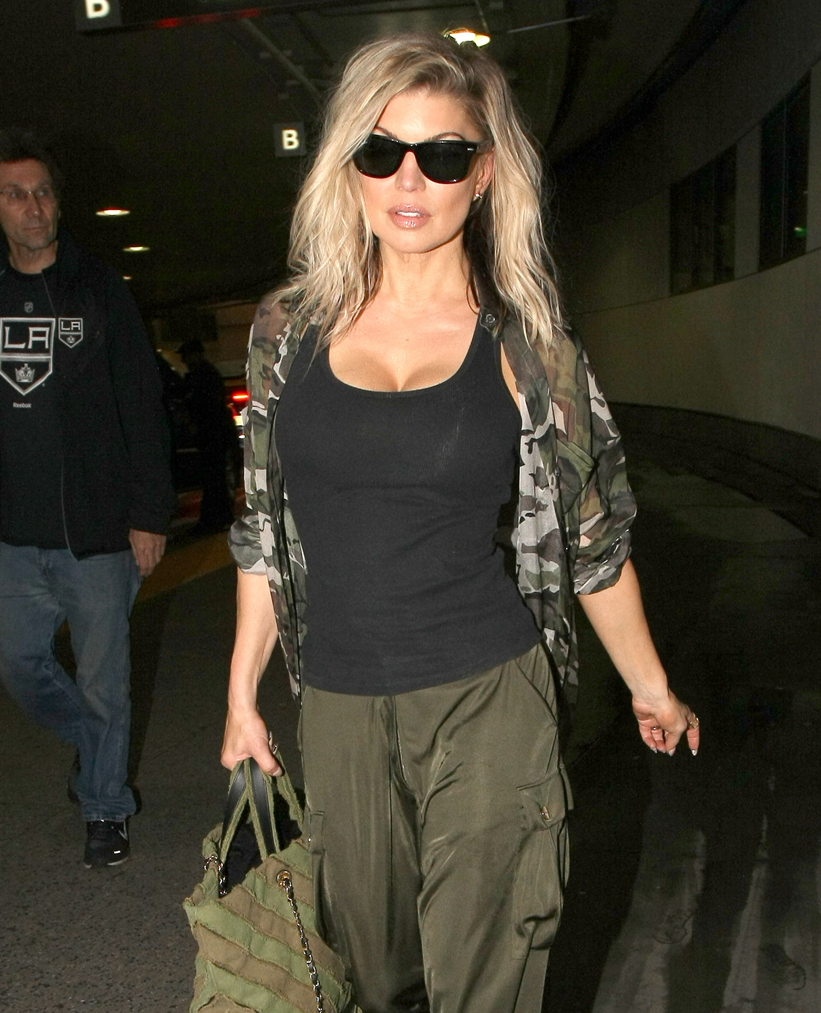"Singer, Fergie can barely contain her assets as she makes an arrival in LA wearing a tiny black tank top and baggy green pants and a camouflage jacket.  The sexy ""Black Eyed Peas"" singer was seen at LAX."
