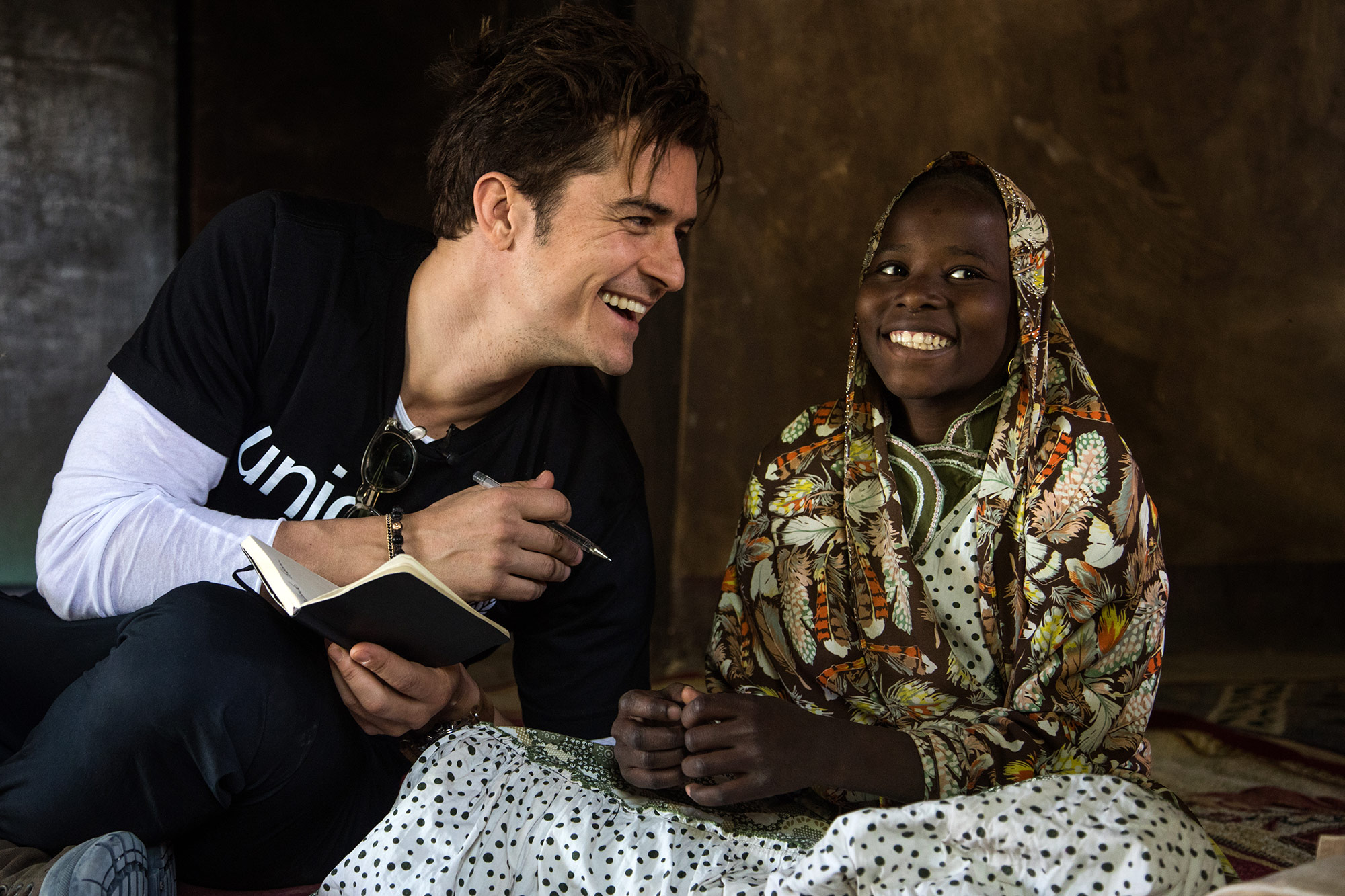 UNICEF Goodwill Ambassador Orlando Bloom (left) smiles as he speaks with twelve-year-old Eta Ibrahim at her family's home, where she lives with her father - the village chief, and her four siblings, in Bosso, Niger, Sunday 19 February 2017. Eta remembers the attacks vividly. It was the 6th of February 2015 around 7AM when she first heard the shootings. Her father and older brother went hiding in the bush while she waited in fear. Around 8AM, Boko Haram forced the door of her home and lined them up in the courtyard, looking for her father and threatening to kill everyone if they didnít give him up. They eventually left with captives. She cried until exhaustion and fled by foot with her family the next day to YÈbi where they had relatives. She remembers the thirst and the hunger of their journey but when she finally received some food, she couldnít eat. She couldnít sleep for months because of the nightmares where she would see Boko Haram coming after her to kill her. She fled to Diffa where she resumed school but she didnít know anyone there and felt lonely. Her mother became ill while they were displaced and eventually died. In October 2016, she finally went back to Bosso where she feels much better. She has resumed her education, starting 7th grade with her friends. She now sleeps better. One day, she dreams of becoming a doctor to help the sick and wounded. In late February 2017, UNICEF Goodwill Ambassador Orlando Bloom travelled to Diffa, south-east Niger, to highlight the ongoing humanitarian crisis in West Africaís Lake Chad Basin (Niger, Nigeria, Chad, Cameroon). Boko Haram violence has caused huge population displacements, leaving hundreds of thousands of children in a critical situation, out of education and at risk of malnutrition. Across the four countries, 2.3 million people are now displaced, making this one of the fastest growing displacement crises in Africa. The Diffa region currently hosts over 240,000 internally displaced people, refug