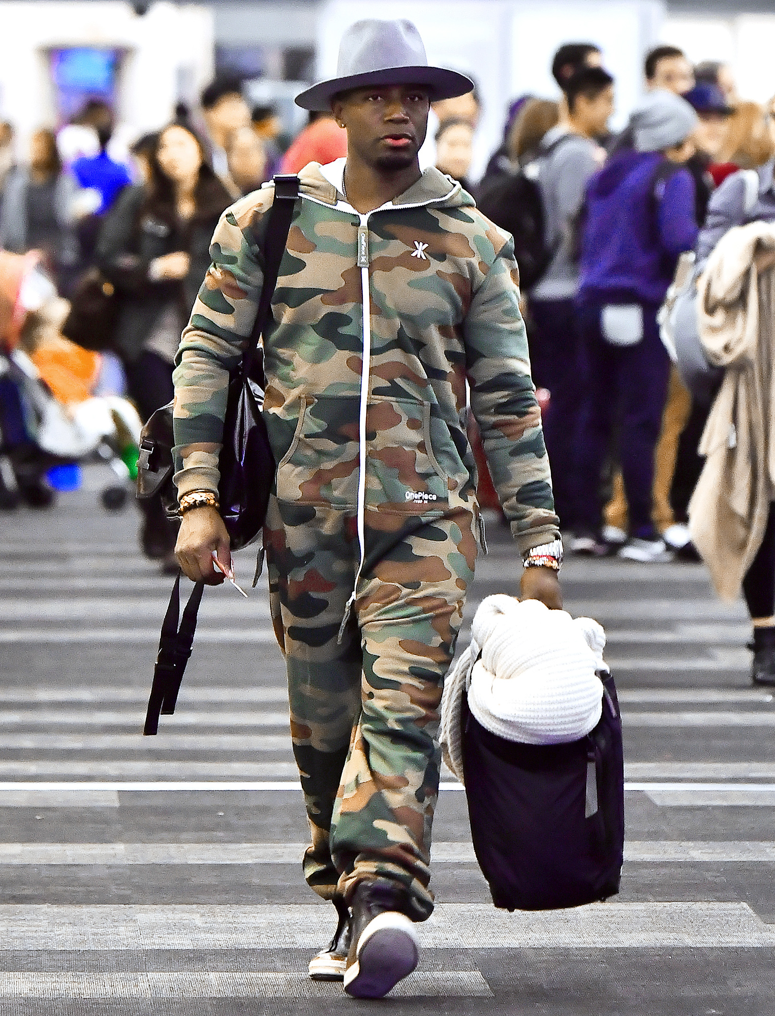 EXCLUSIVE: Taye Diggs spotted wearing a camouflage onesie and a big fedora hat while catching a flight out of LAX in Los Angeles