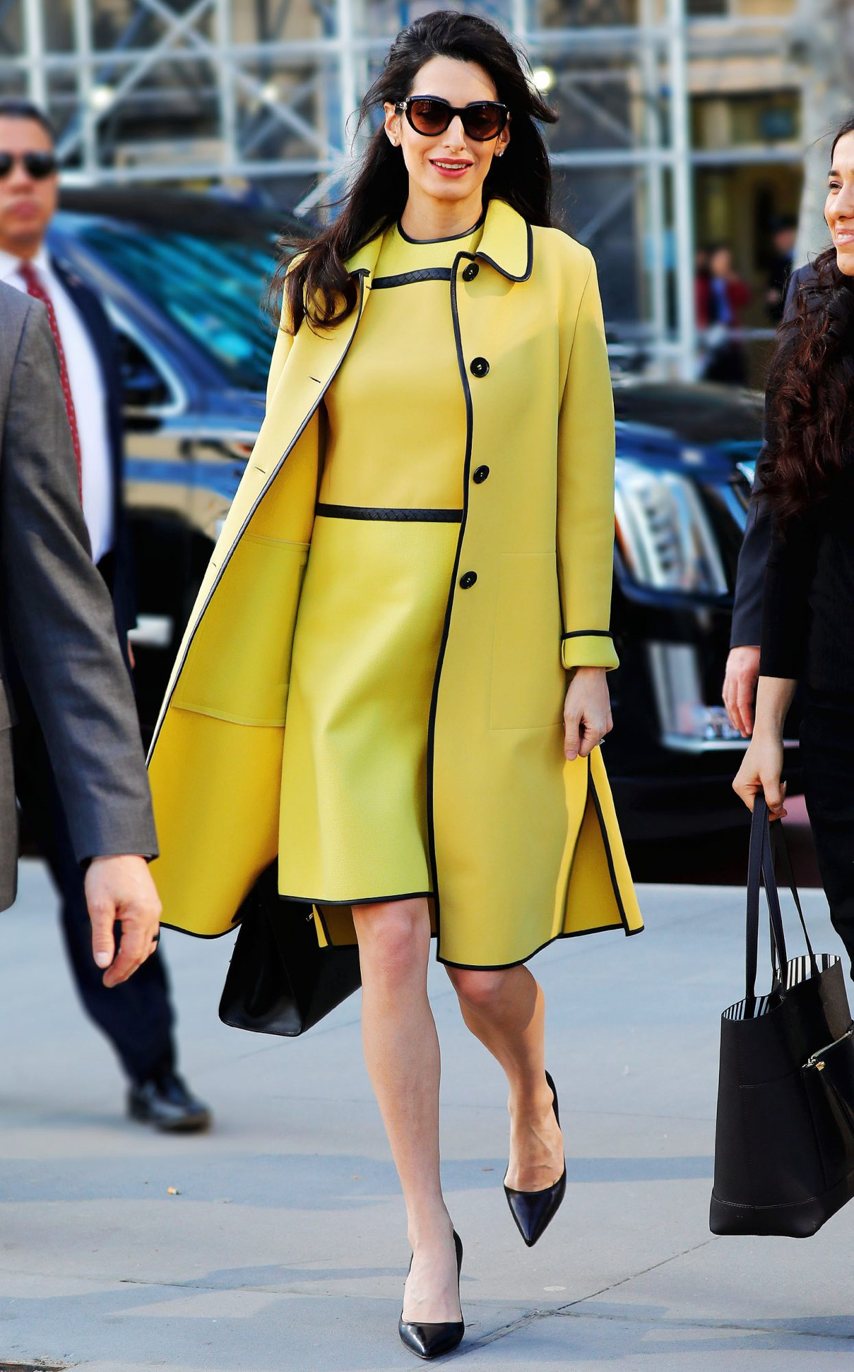 Amal Clooney shows off her pregnant belly in a dazzling canary yellow outfit when walking to the UN in New York