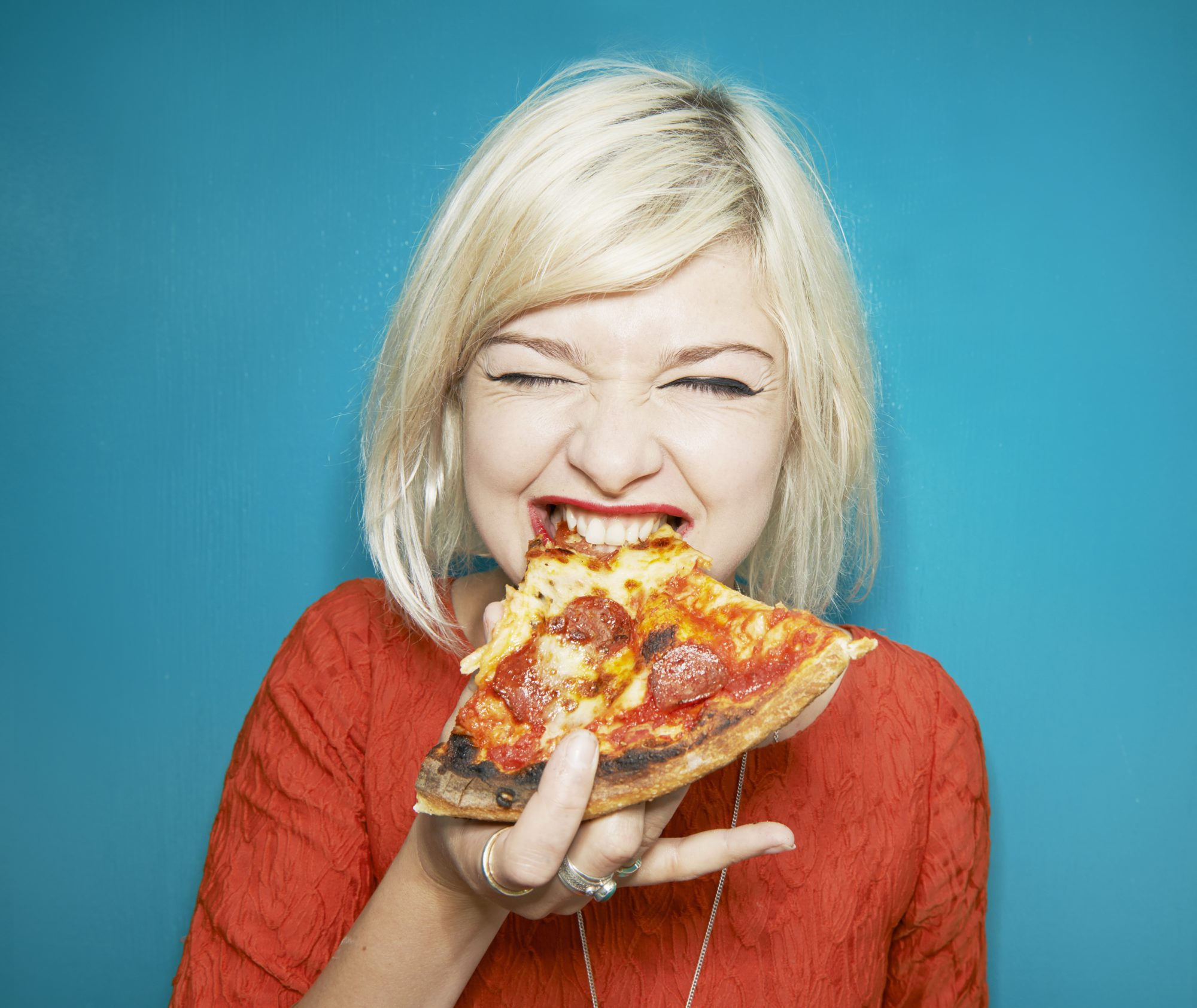 woman eating pizza slice