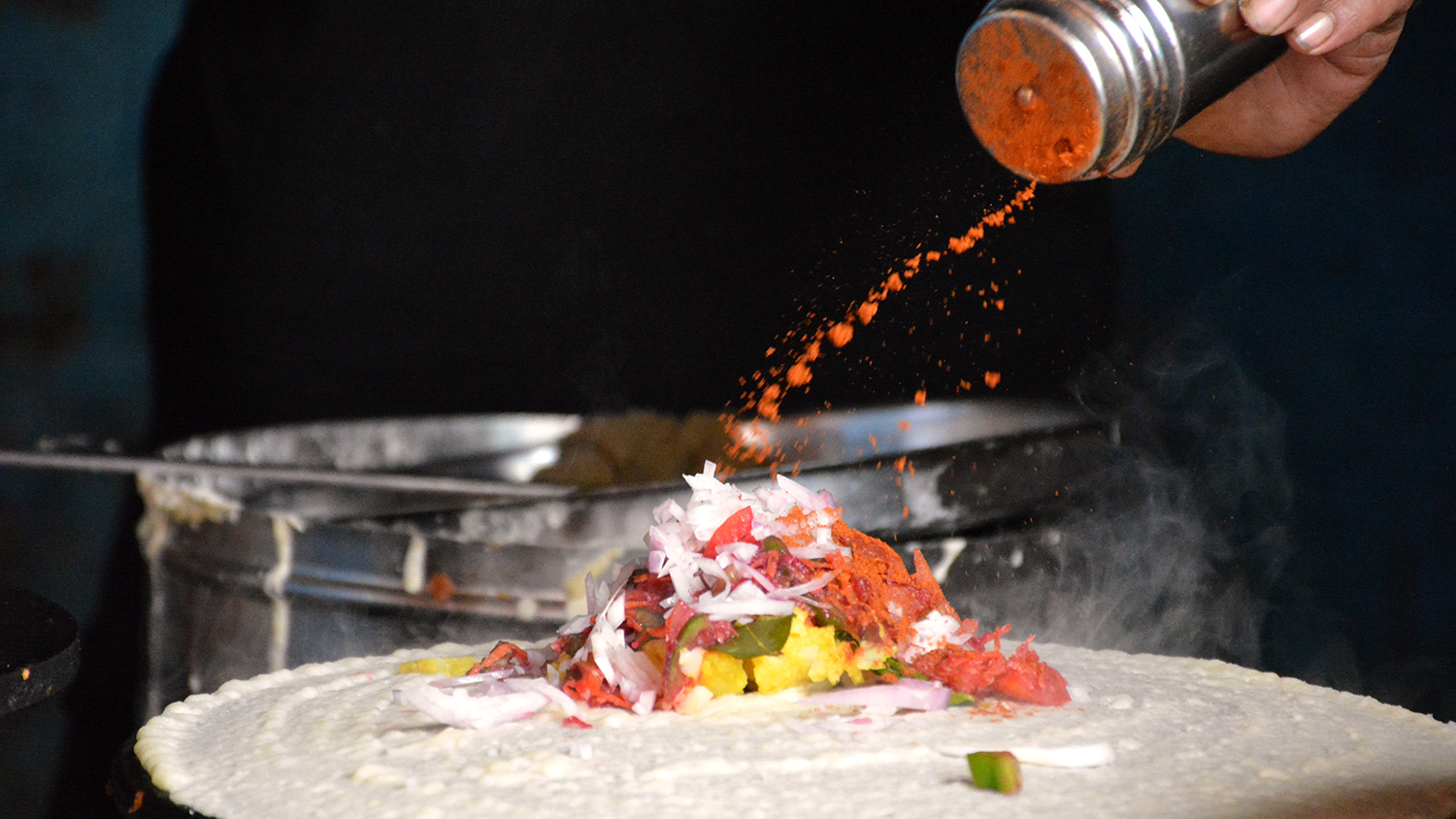 Midsection Of Man Putting Spice On Dosa