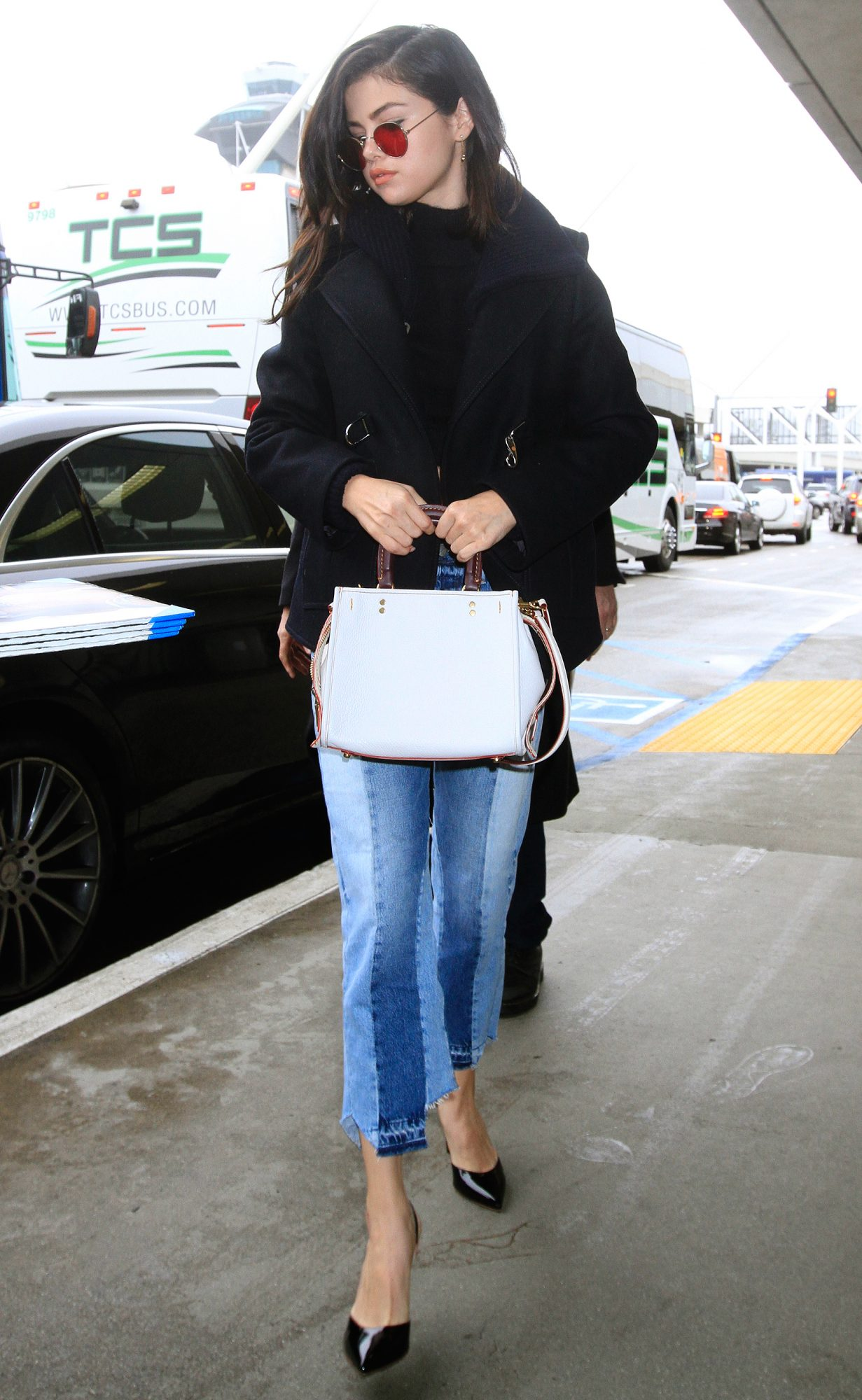 Selena Gomez shows off her toned stomach in a black midriff turtleneck sweater, two-toned blue jeans, black pumps and a long coat with round sunglasses.