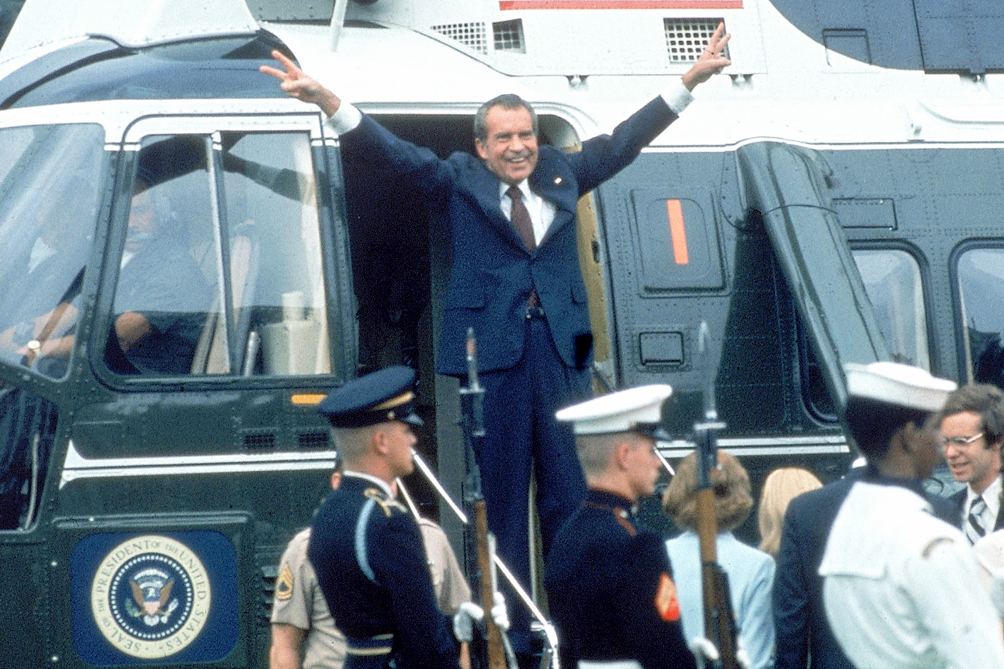 Pres. Richard Nixon w. arms outstretched w. veed f