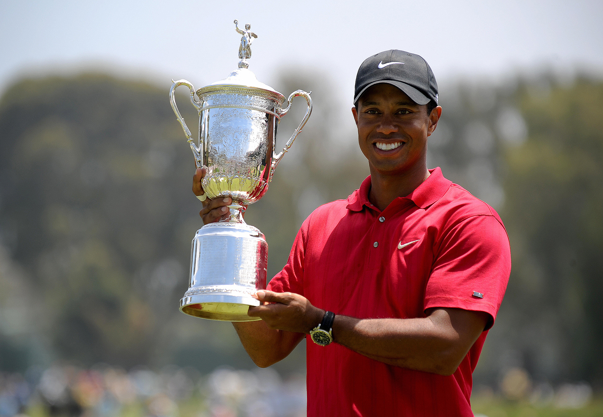 Tiger Woods of the US holds his trophy a