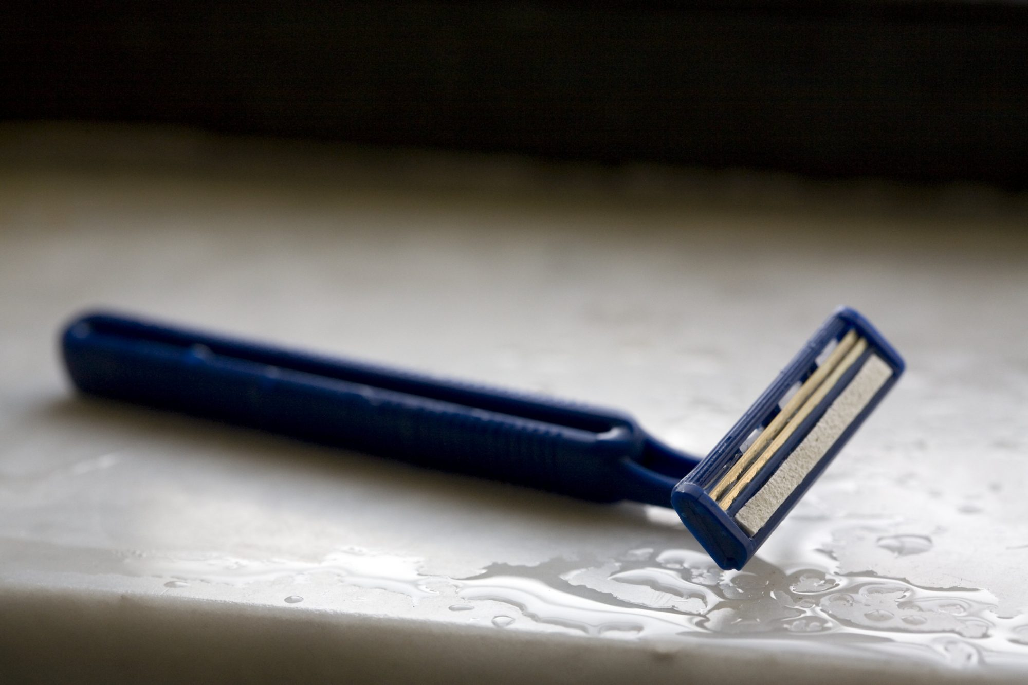 Disposable razor on wet surface, close-up