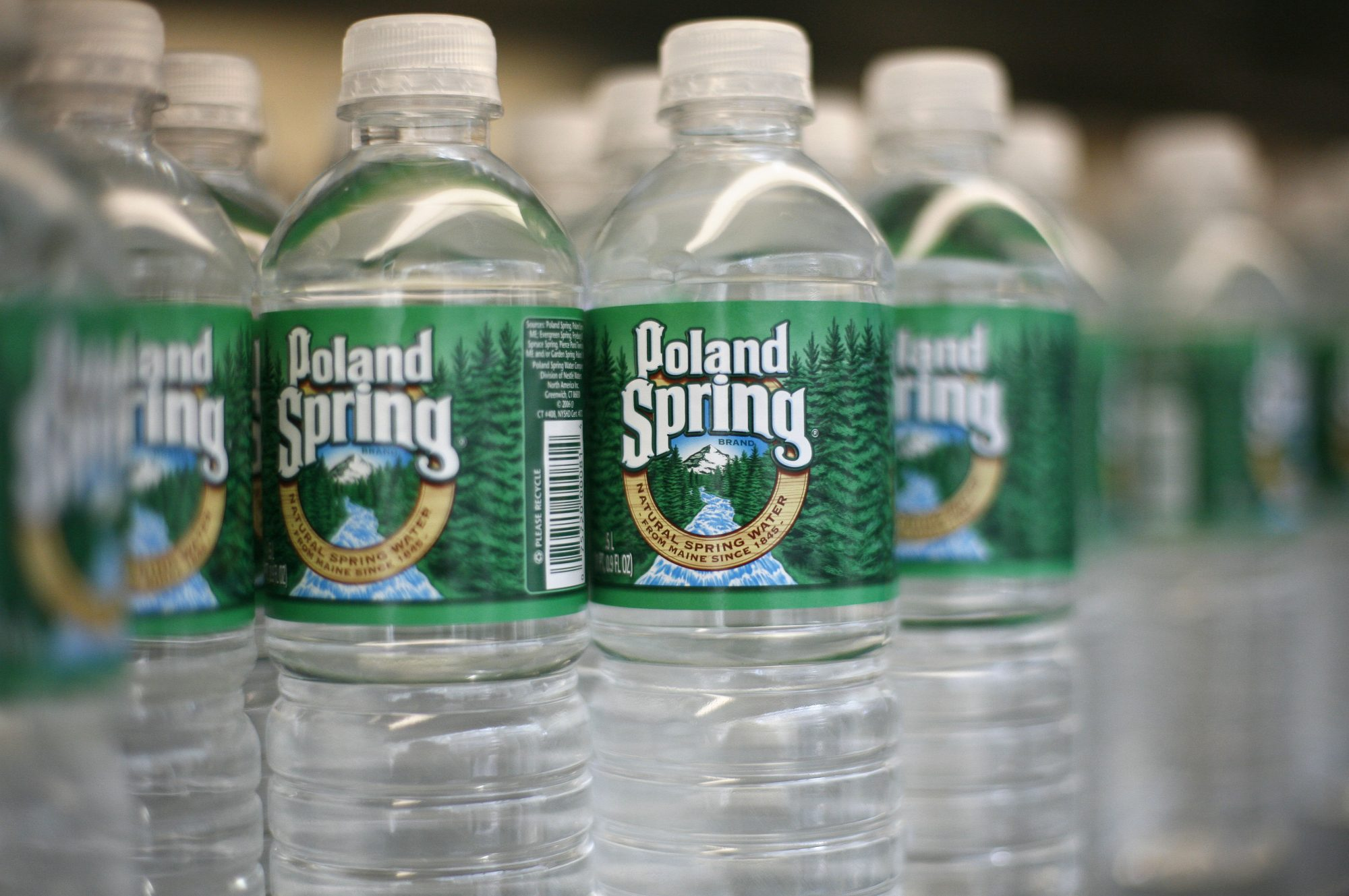 Bottles of Poland Spring water, are arranged on a shelf in N