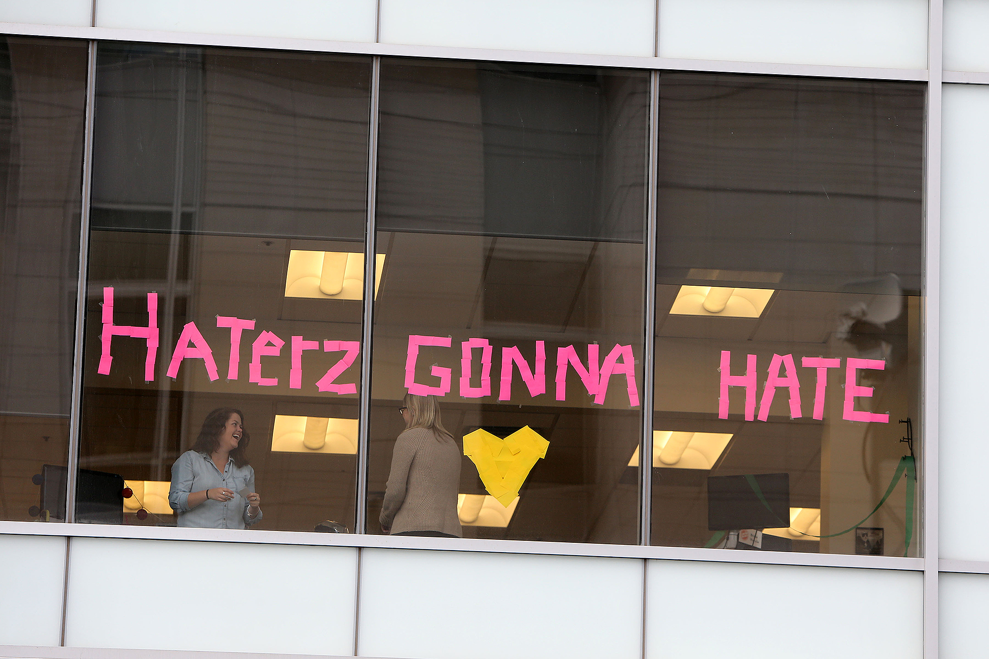 A 'Haterz Gonna Hate' sign appears in the office building opposite the court where the Taylor Swift trial continues in Denver, Colorado.