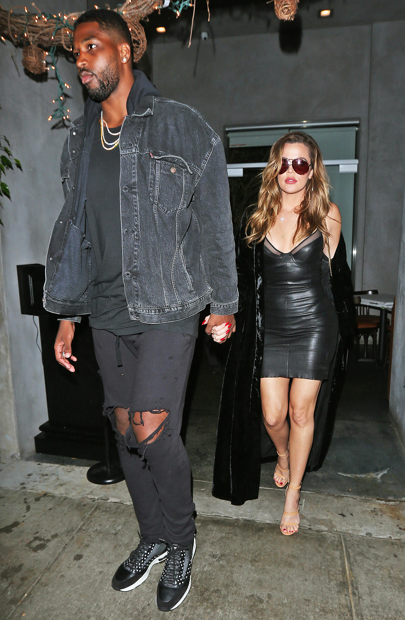EXCLUSIVE: KhloÈ Kardashian wears a black leather dress with a long robe as she and Tristan Thompson have a romantic dinner at Il Pastaio restaurant