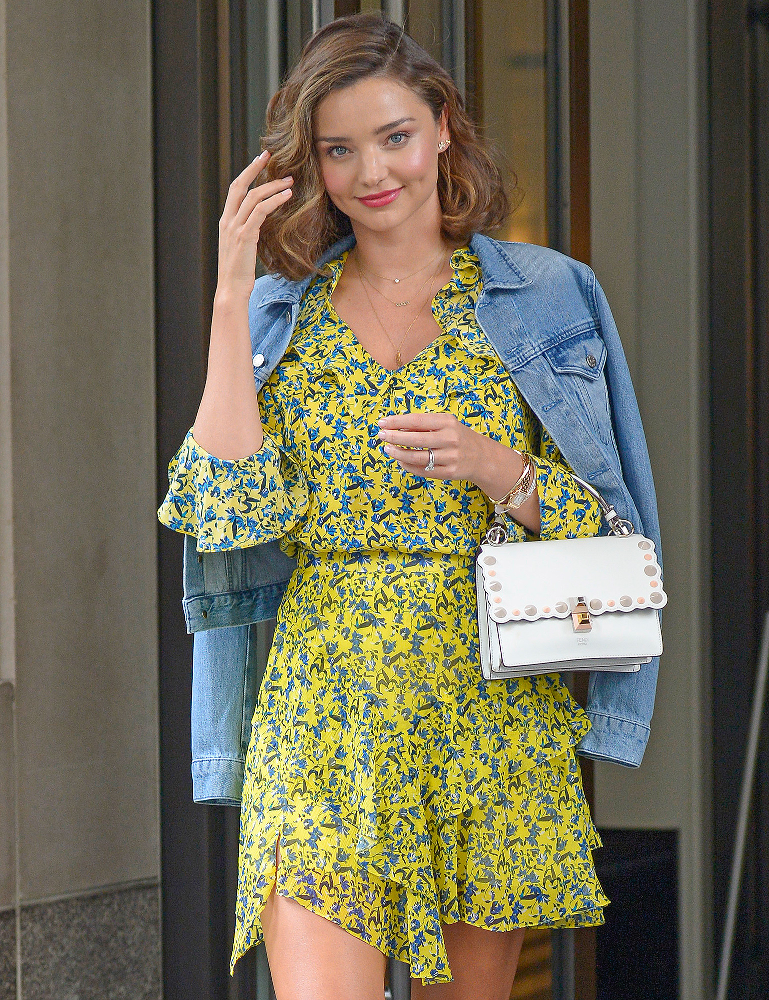 Miranda Kerr wears a yellow floral dress accented with denim jacket as she heads out of her hotel in New York City