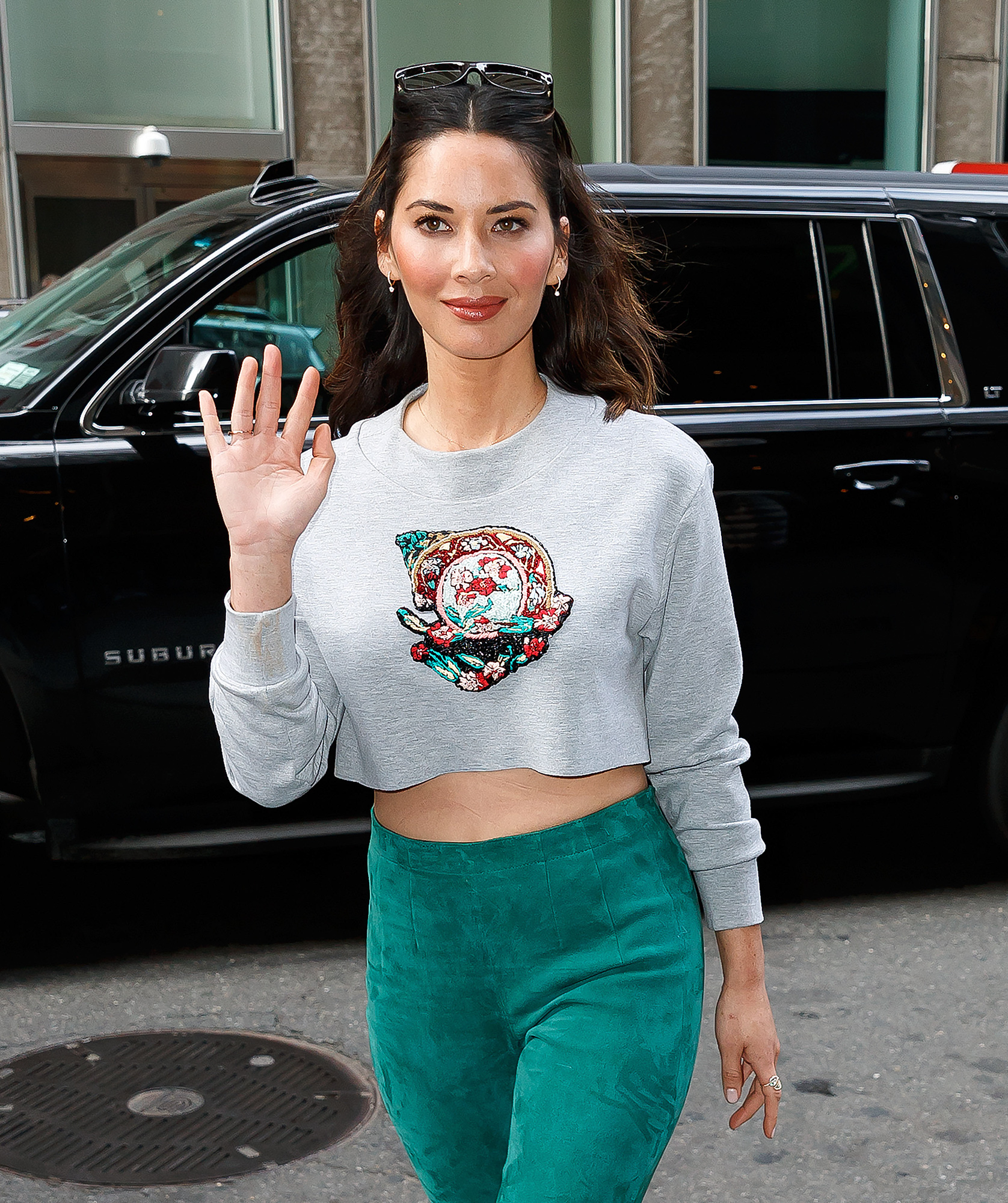 Olivia Munn wears a cropped sweatshirt and turquoise pants in New York