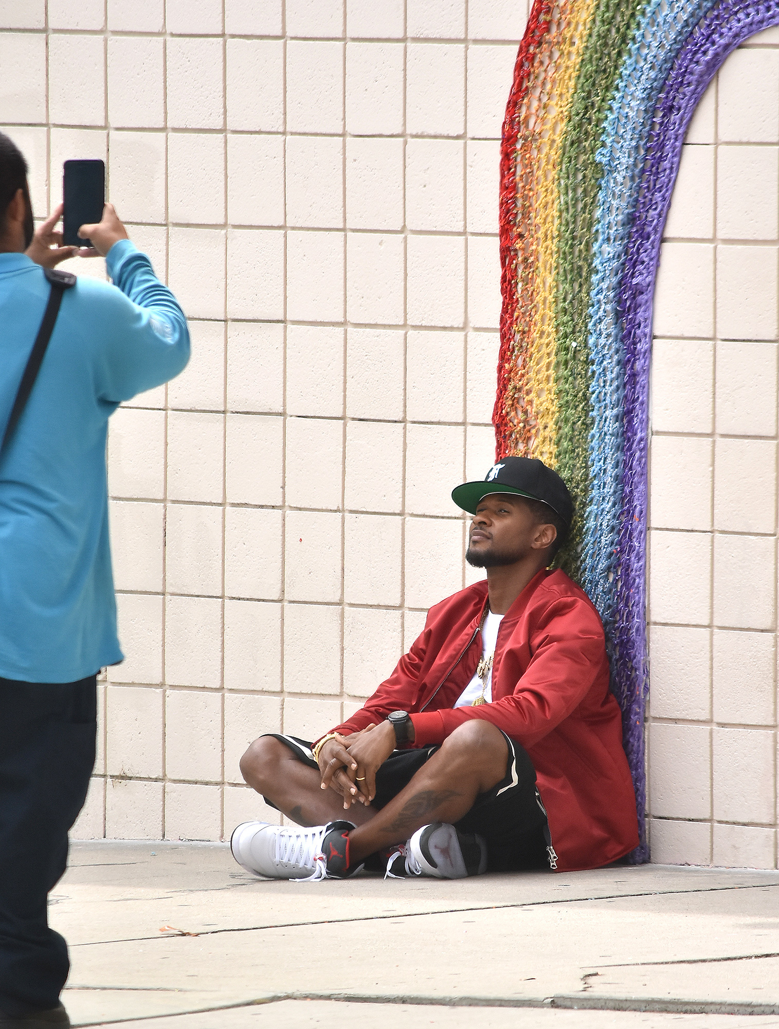 Usher Poses for Photos Under a Rainbow Designed Mural