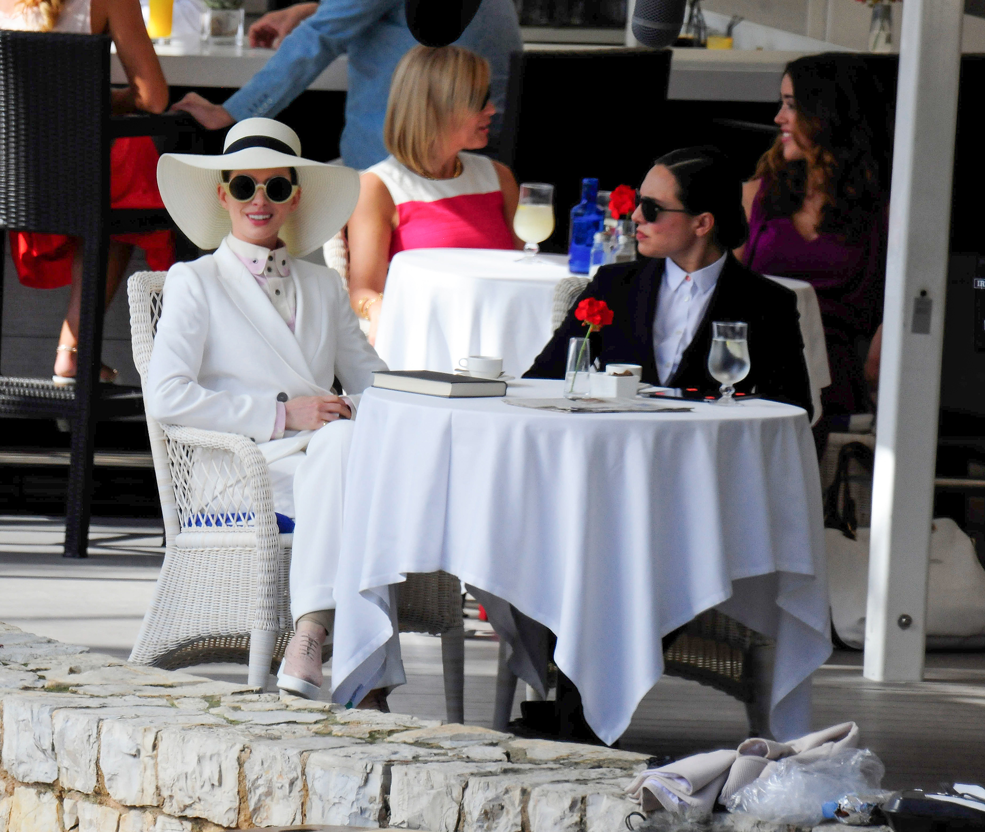 Anne Hathaway wearing a white double breasted suit and large floppy hat while shooting her new movie Nasty Women in Mallorca