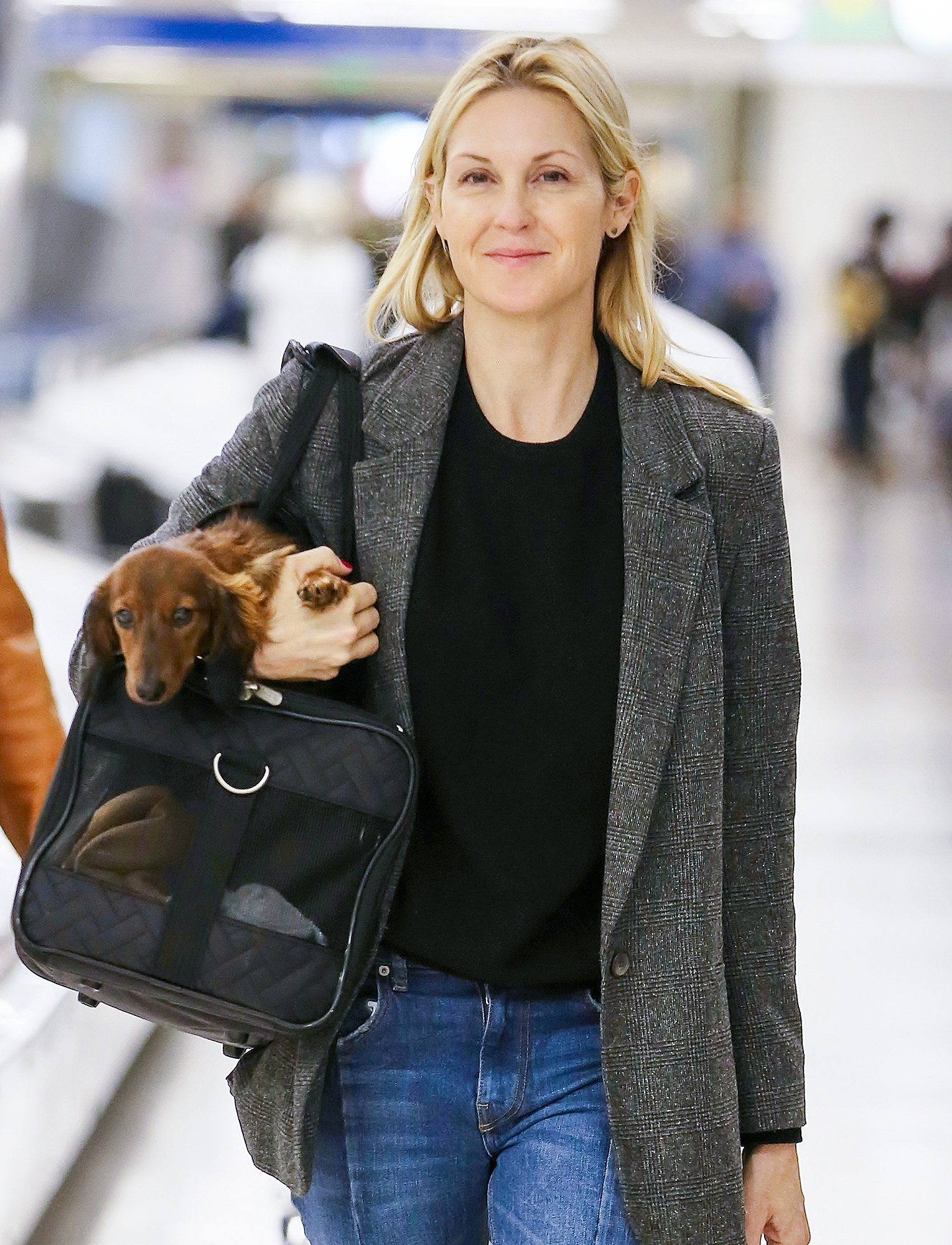 EXCLUSIVE: Makeup free Kelly Rutherford gives her dog a lift at LAX Airport in Los Angeles