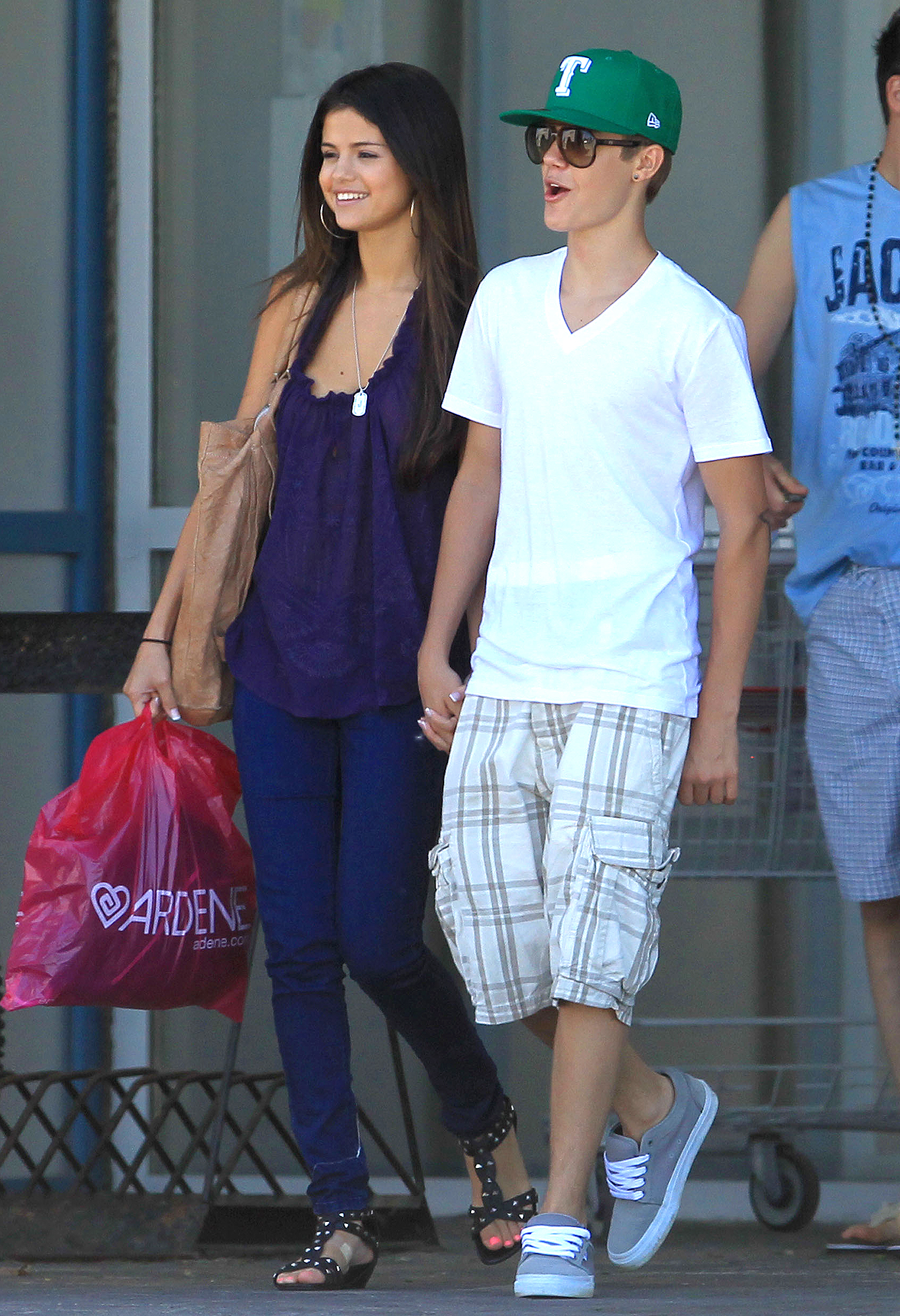 Justin Bieber and Selena Gomez leave a shopping mall hand in hand.