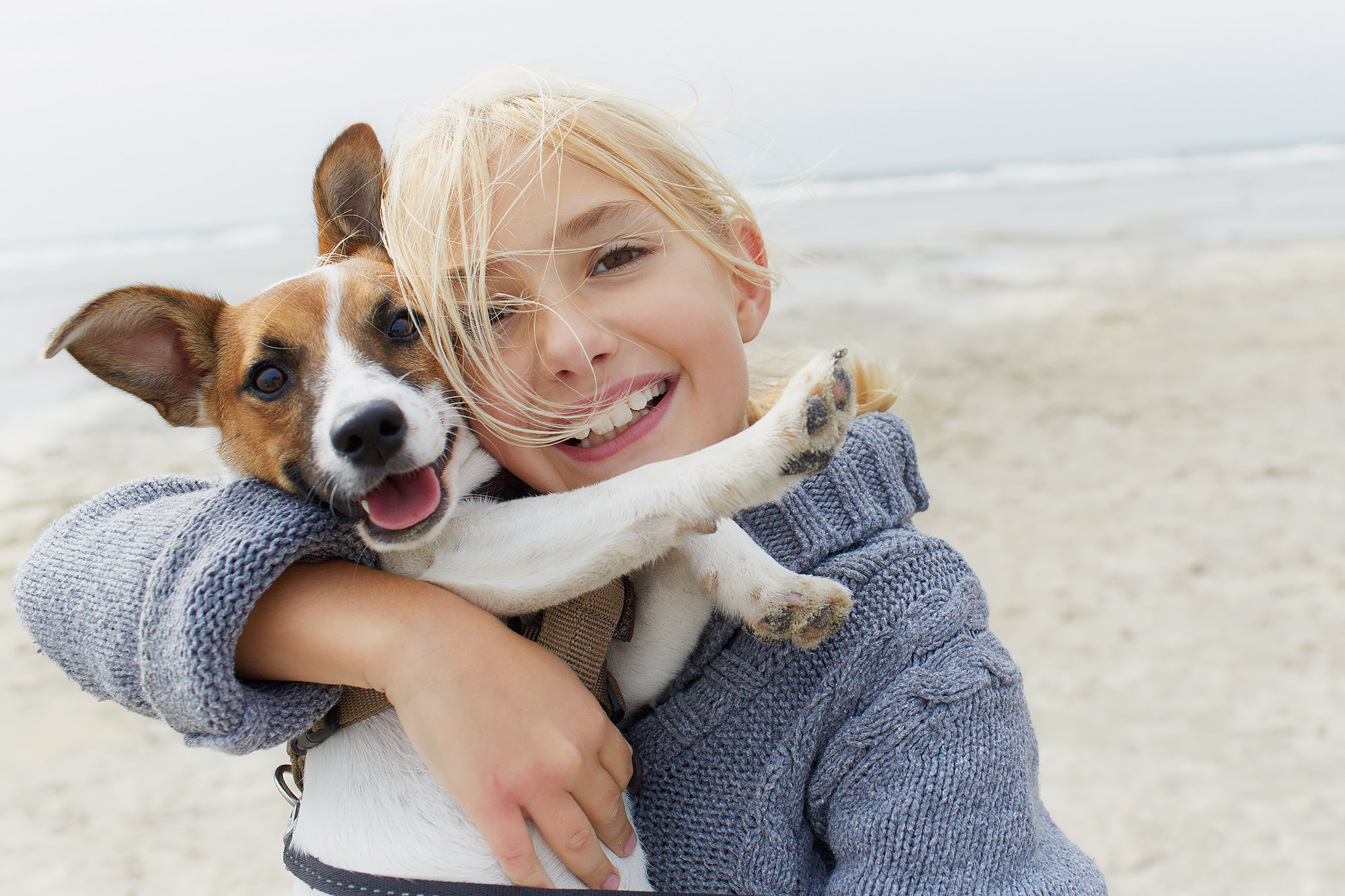 Happy girl hugging dog on the beach, portrait