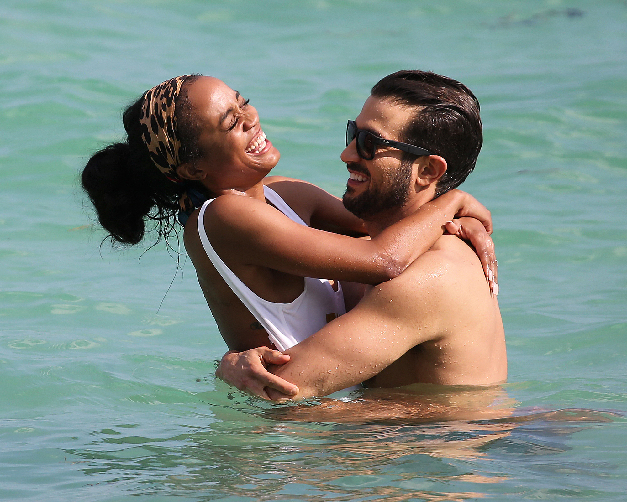 Bachelorette star Rachel Lindsay and finance Brian Abosolo show off their beach bodies and a lot of PDA as they take a dip in the ocean in Miami