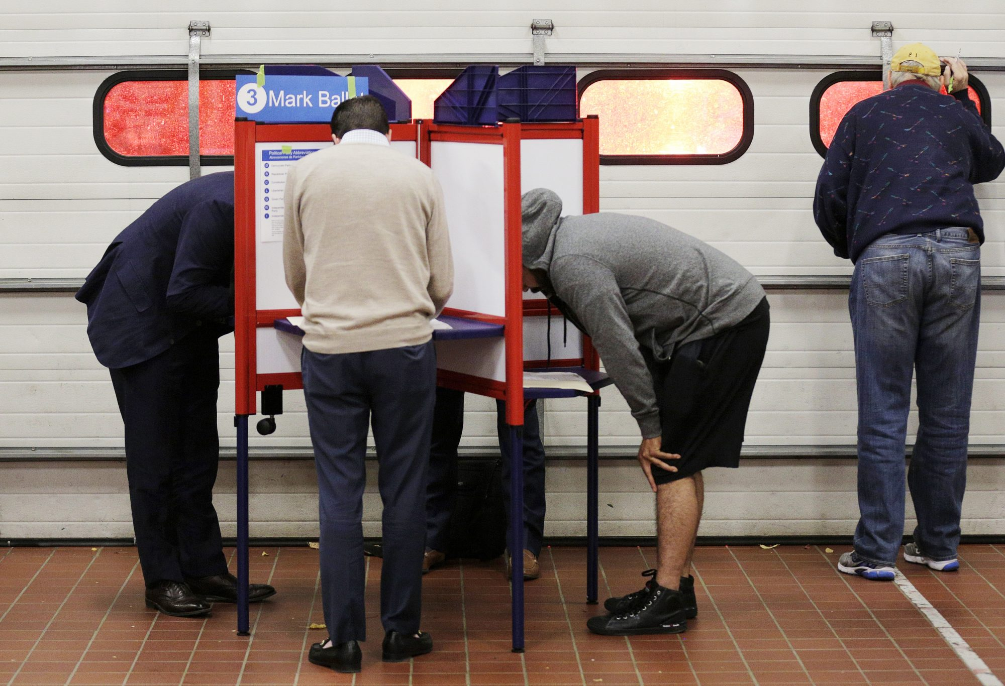 Voters look over their ballots at a fire station while a crew leaves on an emergency call during the U.S. presidential election in Arlington