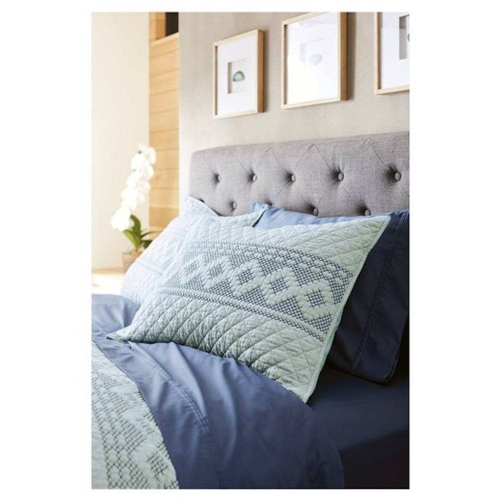 Blue Stitch Pillow on bed
