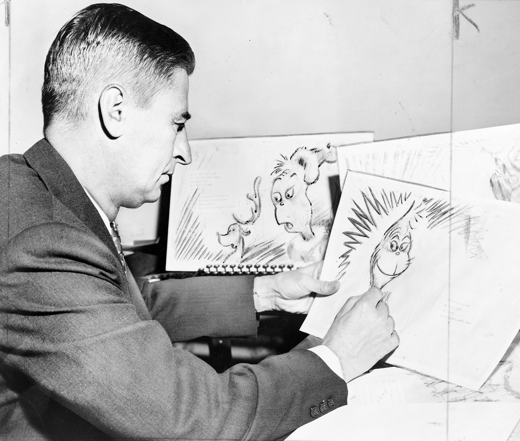 """Theodor Seuss Geisel 1904 ? 1991, American writer, poet, and cartoonist at work on a drawing of a grinch, the hero of his forthcoming book, """"How the Grinch Stole Christmas"""""""
