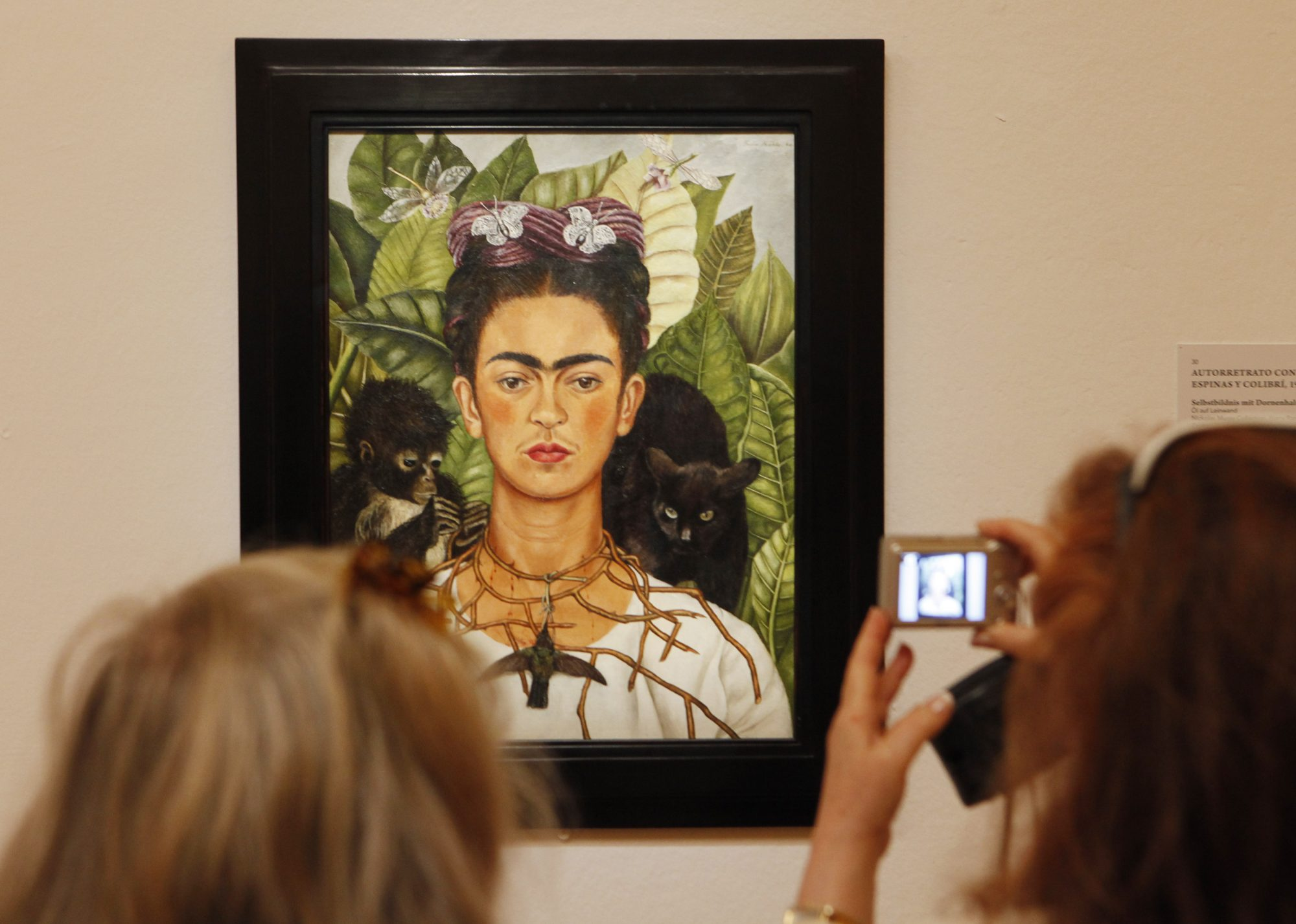 Visitors looks at a painting by Mexican