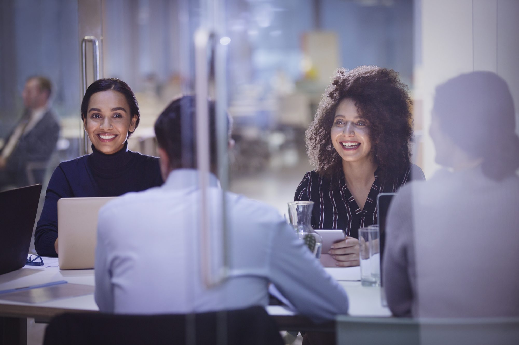 Businesswomen smiling in conference room meeting