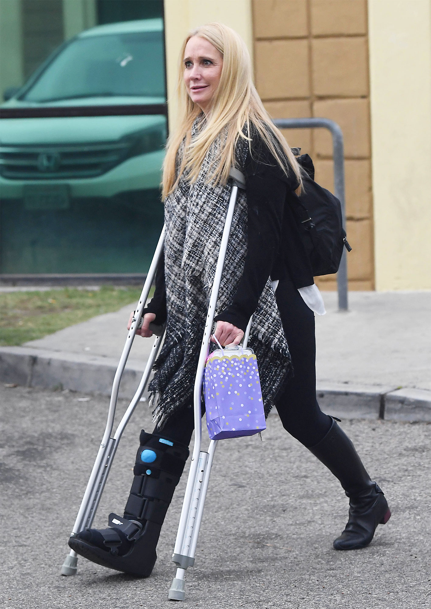 EXCLUSIVE: Kim Richards uses a pair of crutches to walk with a cast on her right leg at niece's birthday party with sister Kyle