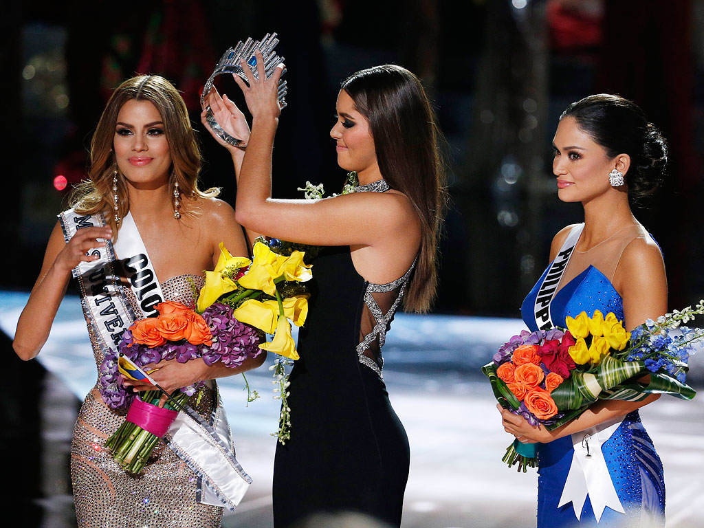Former Miss Universe Paulina Vega, center, removes the crown from Miss Colombia Ariadna Gutierrez, left, before giving it to Miss Philippines Pia Alonzo Wurtzbach, right, at the Miss Universe pageant on Sunday, Dec. 20, 2015, in Las Vegas.