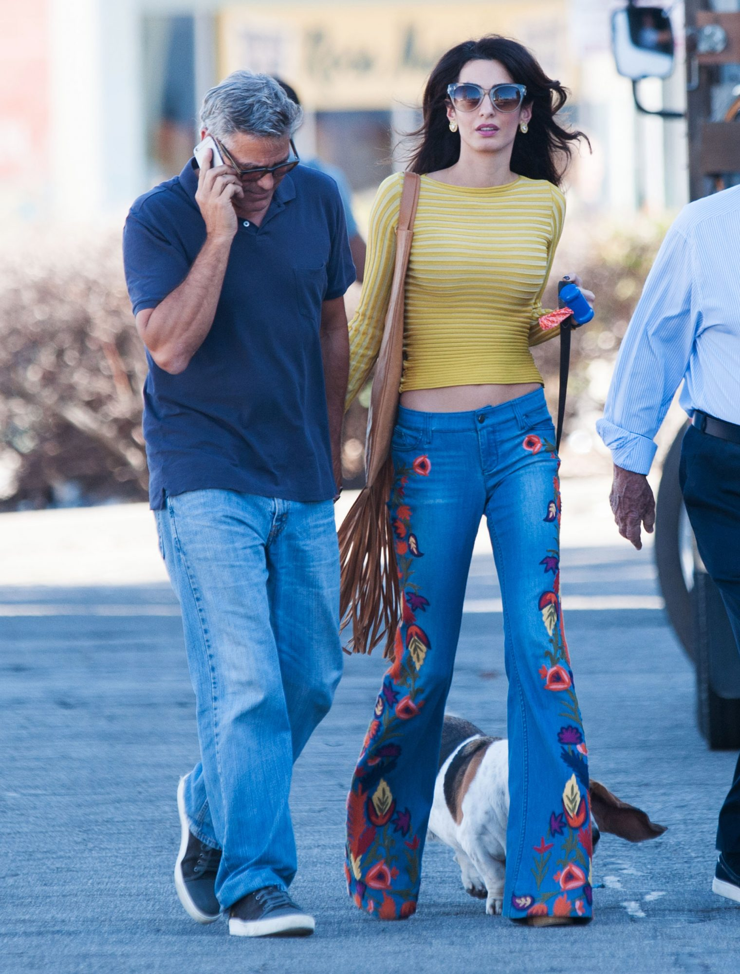 10/20/2016 Amal Clooney is spotted visiting husband George Clooney on the Los Angeles set of Suburbicon today. The 38 year old British-Lebanese lawyer and activist was seen arriving to the Cohen Brothers film set today looking casual in hand painted flared denim jeans paired with a tight fitting yellow crop top. The couple were spotted strolling hand and hand with their pet basset hound. Please byline:TheImageDirect.com