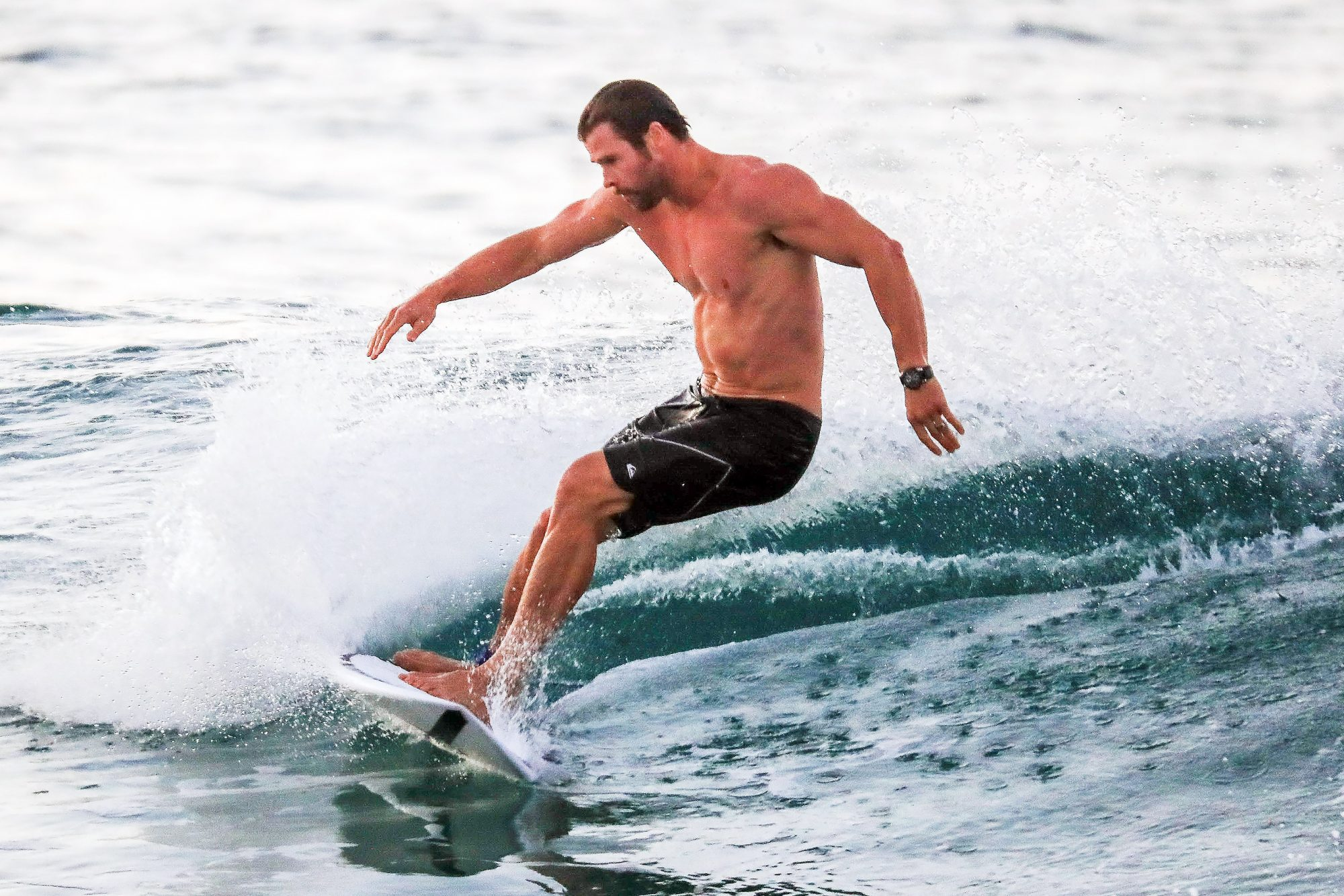 EXCLUSIVE: *NO MAIL ONLINE* Chris Hemsworth enjoys an early evening surf in his hometown of Byron Bay, Australia