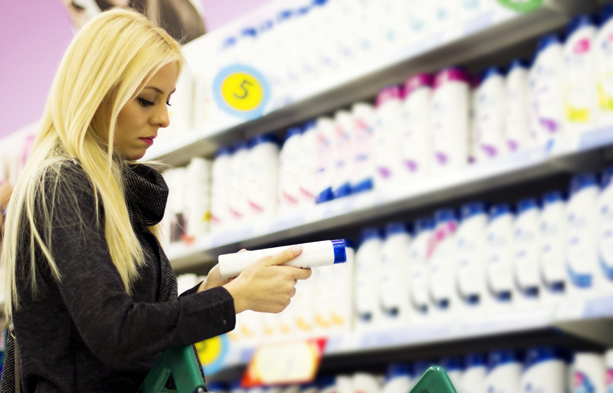 Young woman shopping at the supermarket for hair products