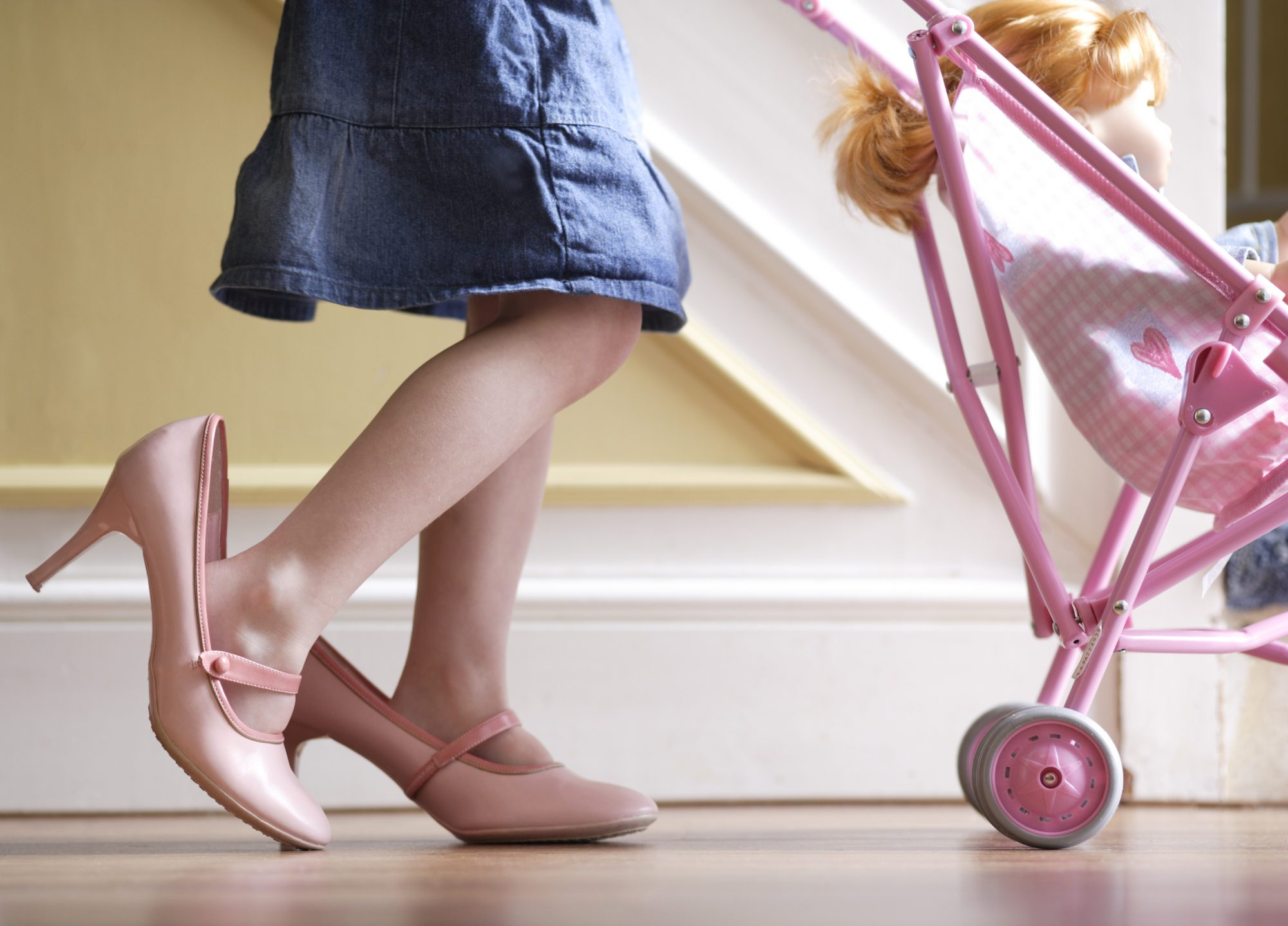 Girl (3-5) wearing adult shoes, pushing doll in pram, low section