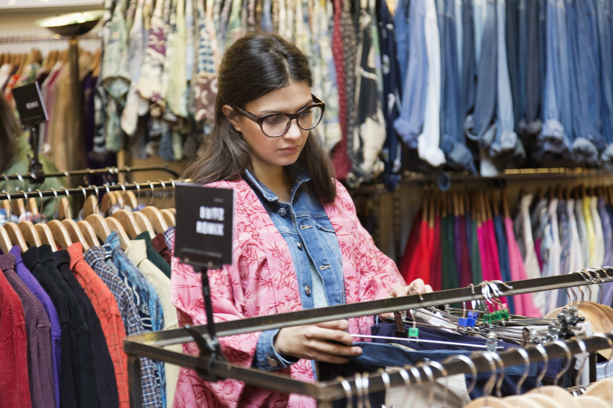 Young female shopper searching vintage clothes stall in market hall