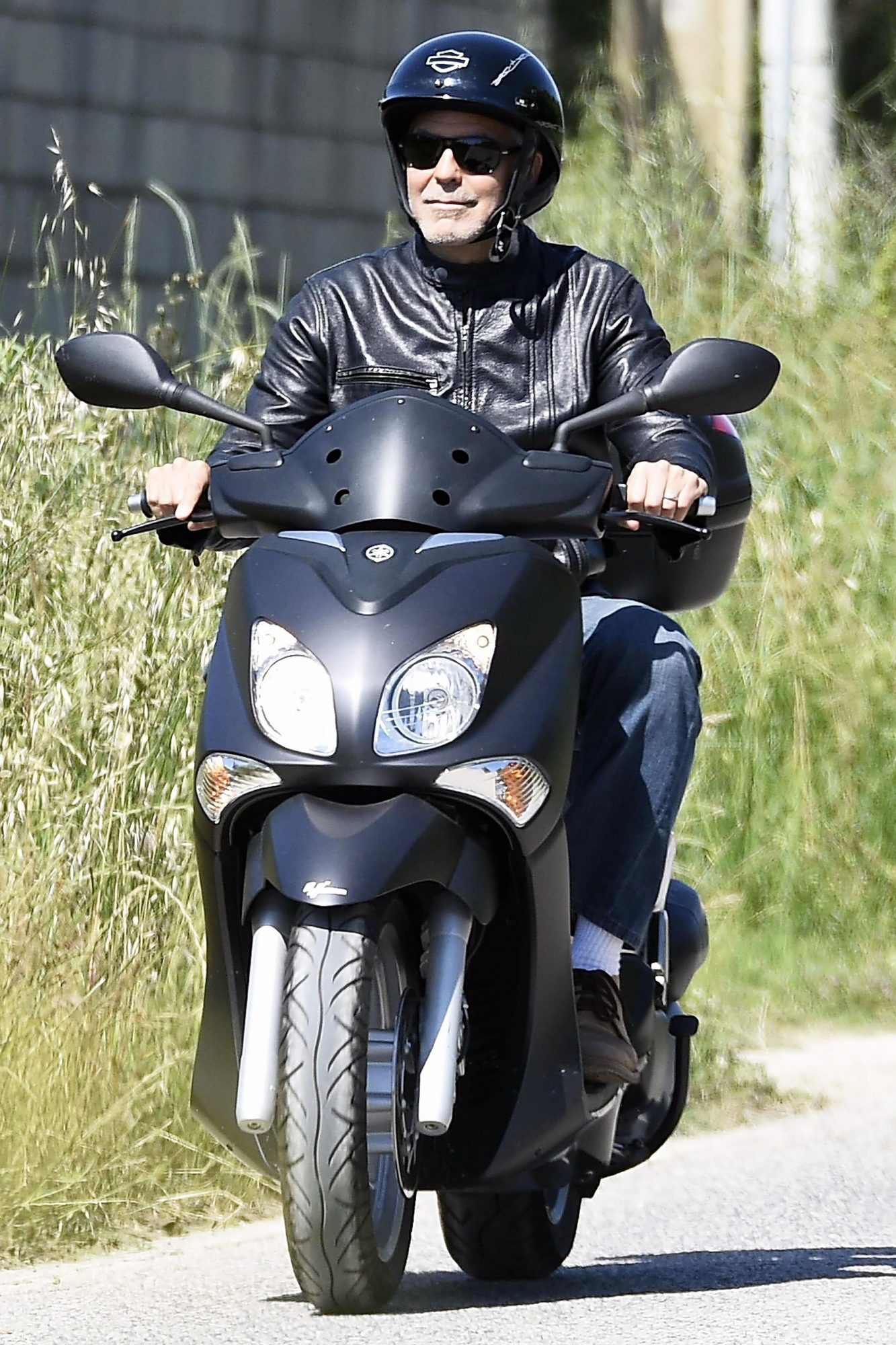 George Clooney cruises the town of Sardinia on a scooter