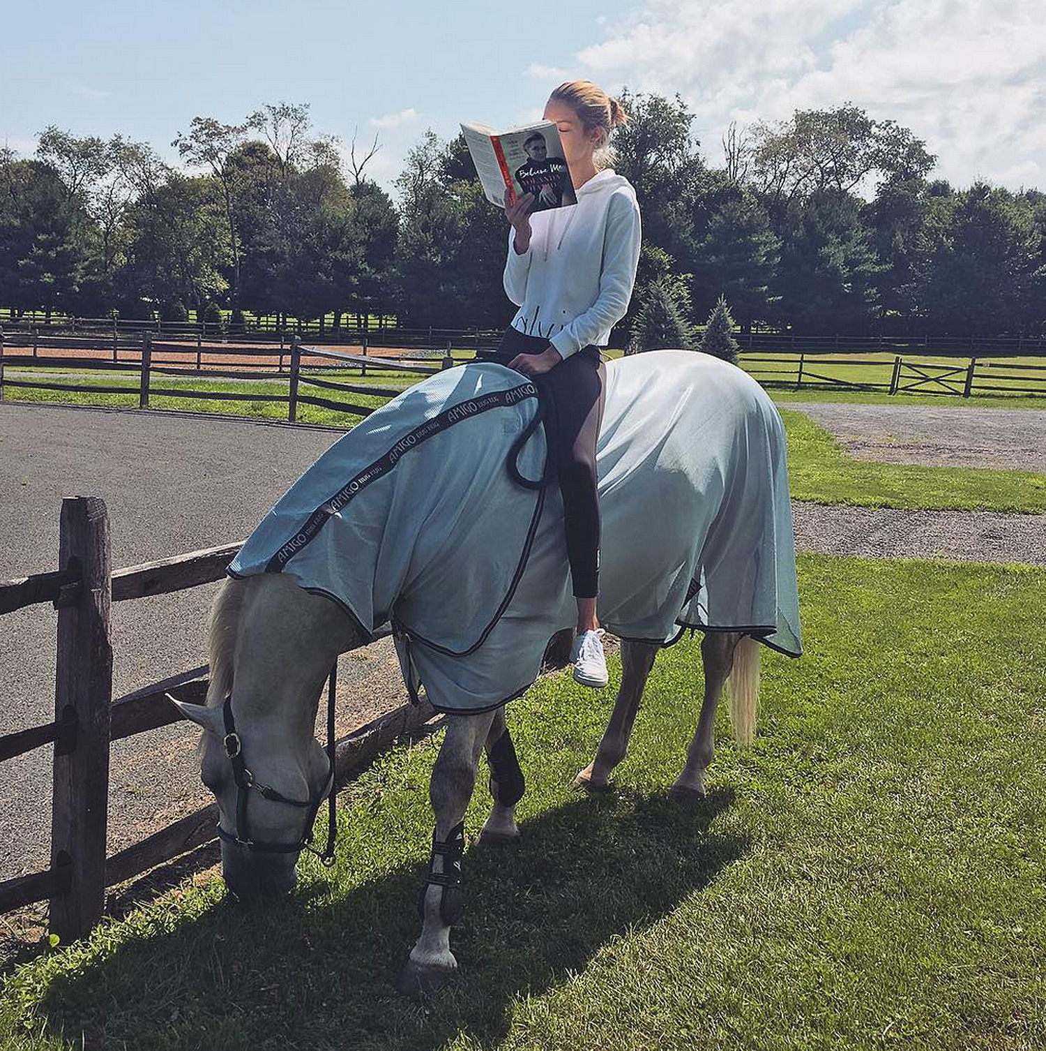 GIGI HADID READS A BOOK WHILE HORSEBACK RIDING