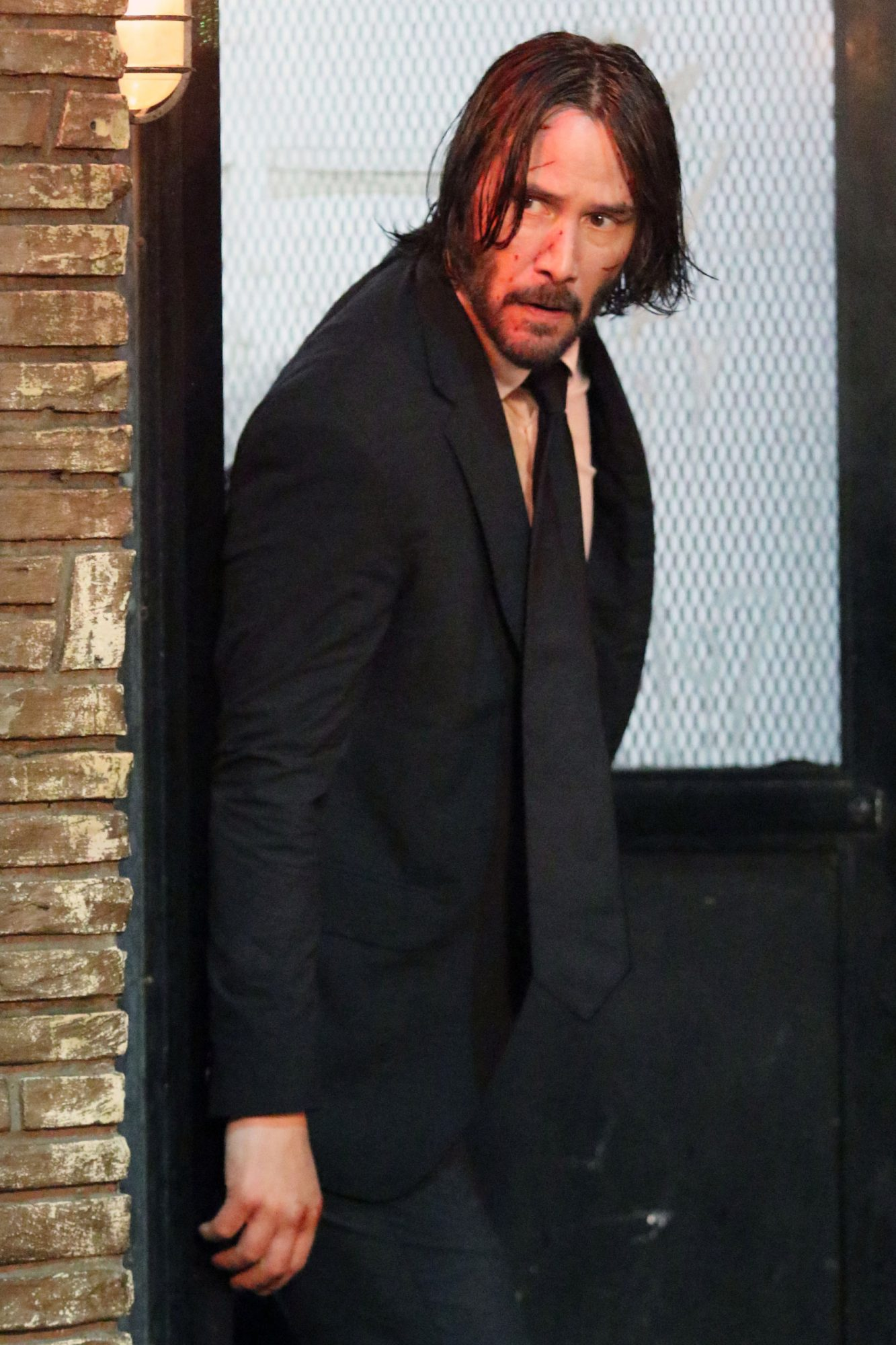 """Keanu Reeves is soaking wet as he shoots an intense running scene in the rain for """"John Wick Chapter 3"""" in NYC"""