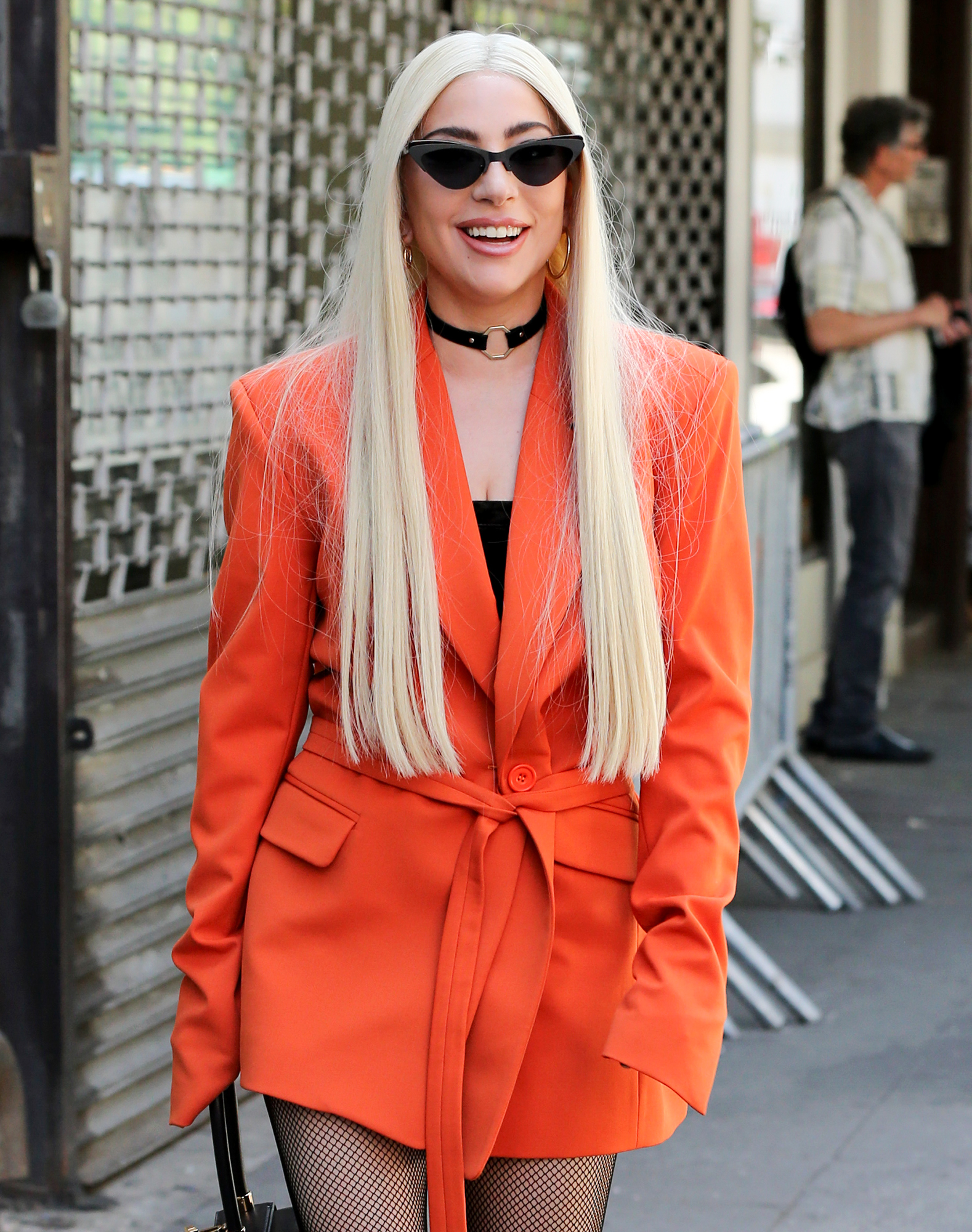 Singer Lady Gaga, wearing an orange suit and platform lace-up boots, walks in Soho in New York City, New York on June 25, 2018.