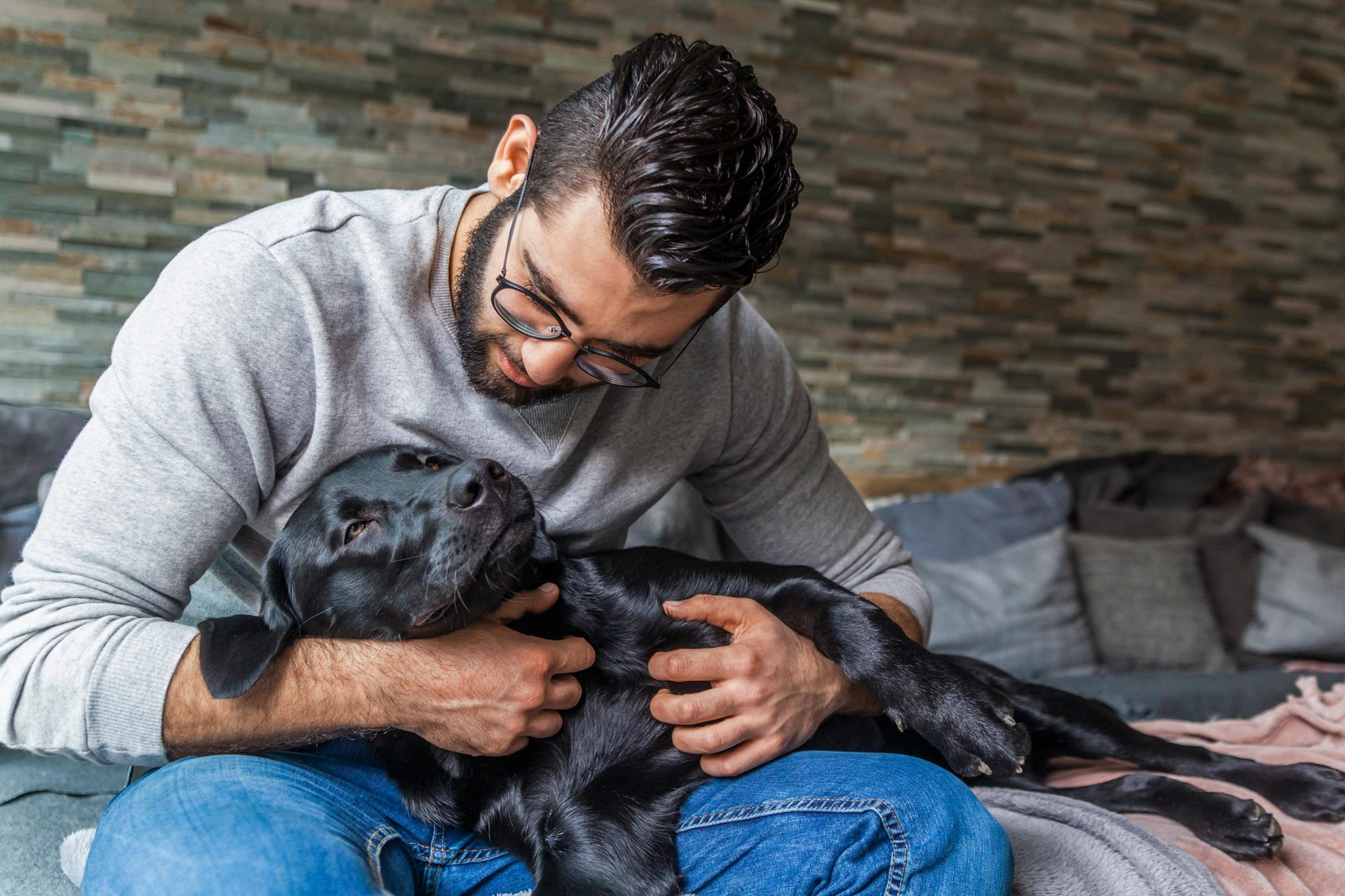 Man cuddling with his dog on the couch at home