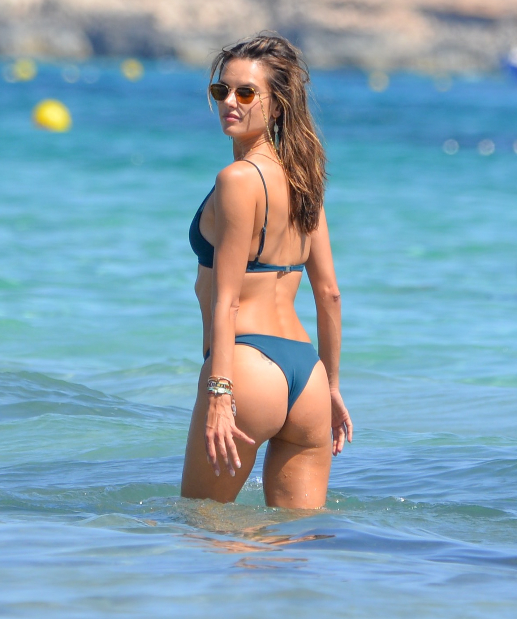 Supermodel Alessandra Ambrosio shows off her rock hard abs and perky posterior in a tiny teal bikini on the beach in Ibiza