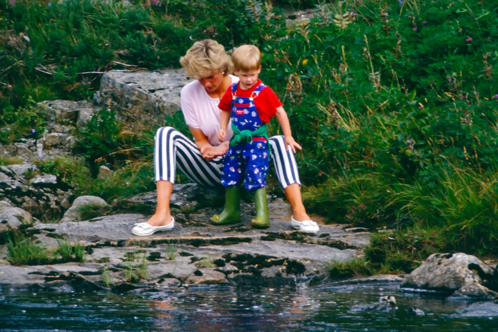 Diana, Princess of Wales, Prince William, and Prince Harry play on the banks of the River Dee, near Balmoral Castle