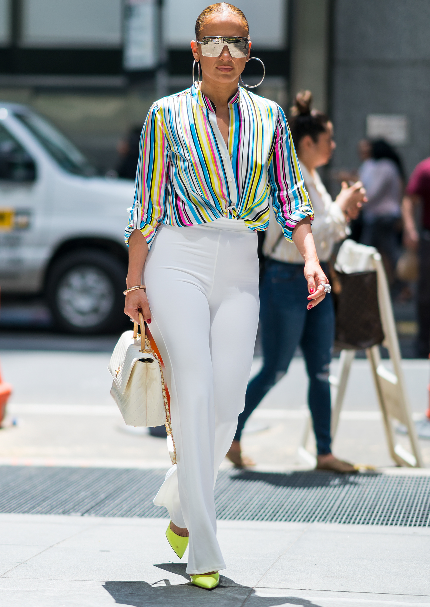Jennifer Lopez is seen wearing a rainbow shirt, white pants with a Chanel handbag, Jennifer Fisher earings and Cartier ring while out for a stroll in New York City