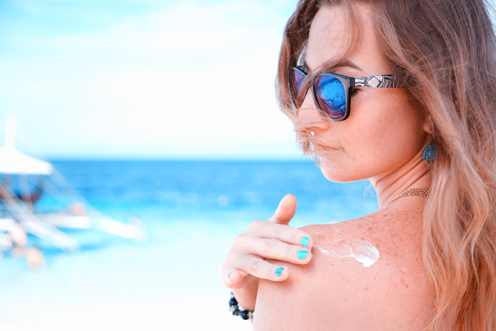 young woman with sunglasses applyng sun protector cream at her hand on the beach close to tropical turquoise sea under blue sky