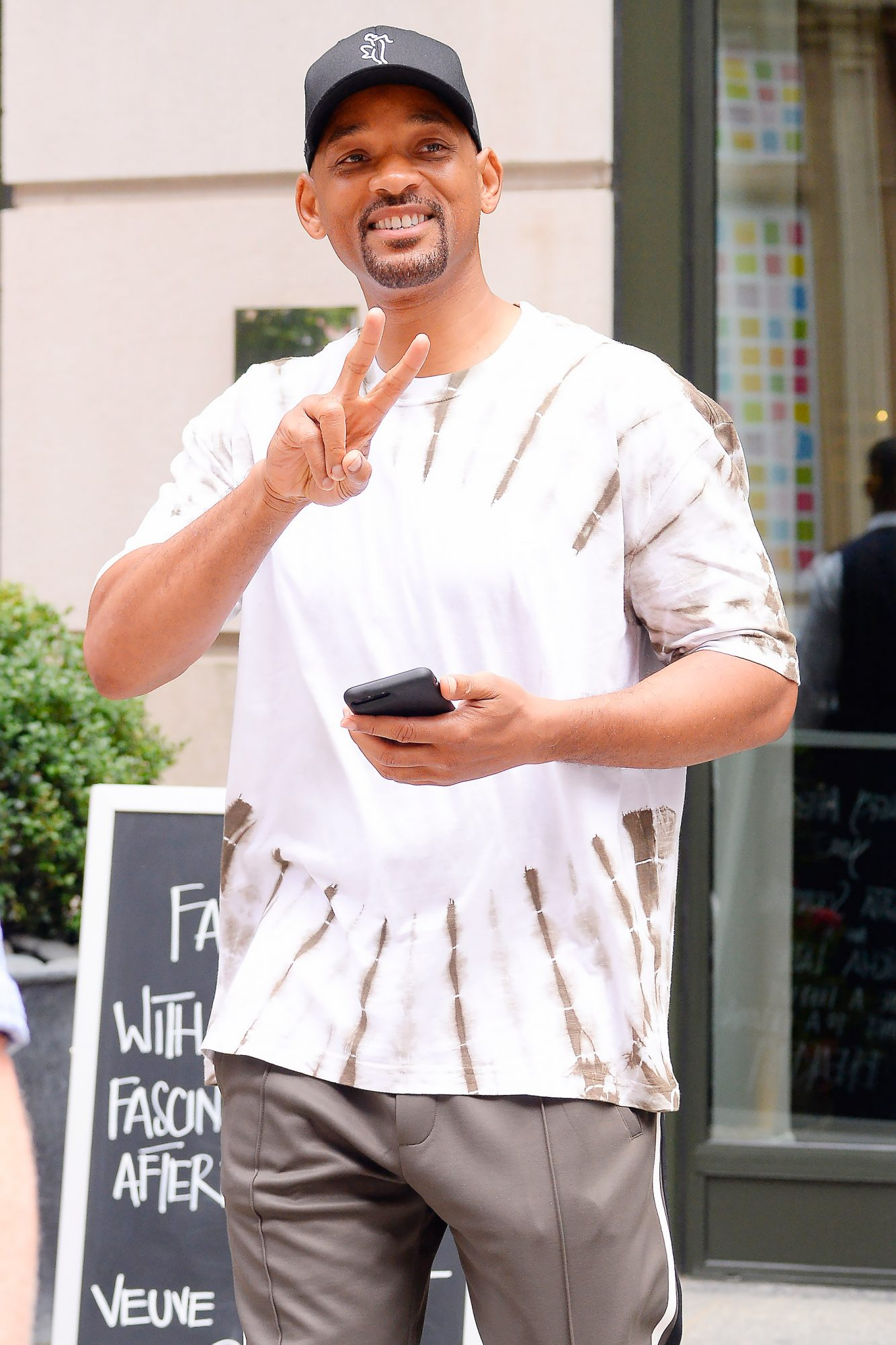 Will Smith gives the peace sign to photographers outside his hotel in New York City