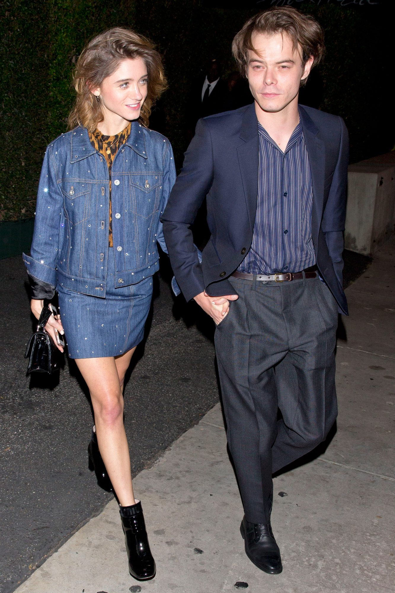 Stranger Things stars, Natalia Dyer and Charlie Heaton hold hands as they leave the 'MIU MIU' clothing launch in West Hollywood, CA