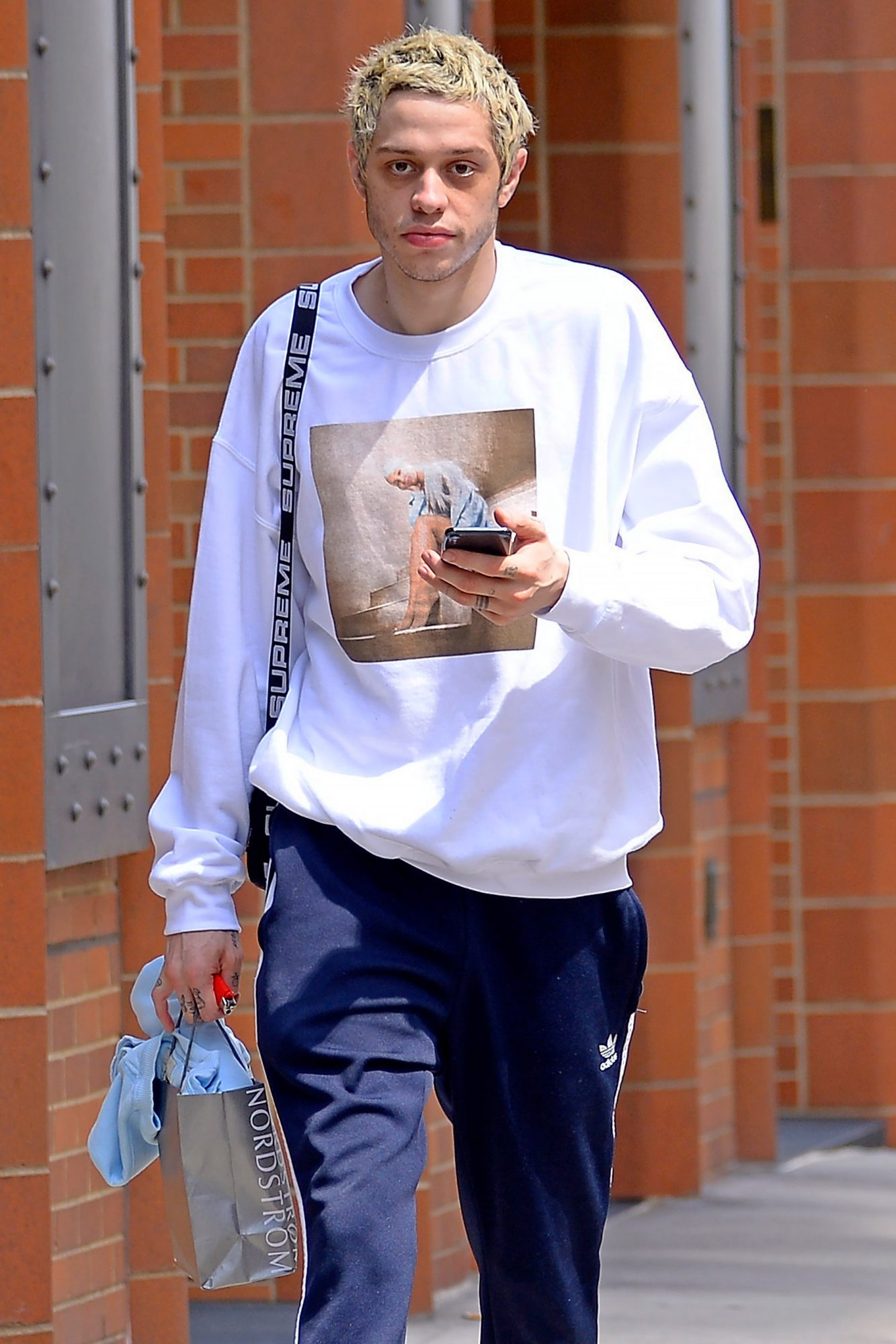 EXCLUSIVE: Pete Davidson wears a sweater with fiancee Ariana Grande's picture in front while out in New York City