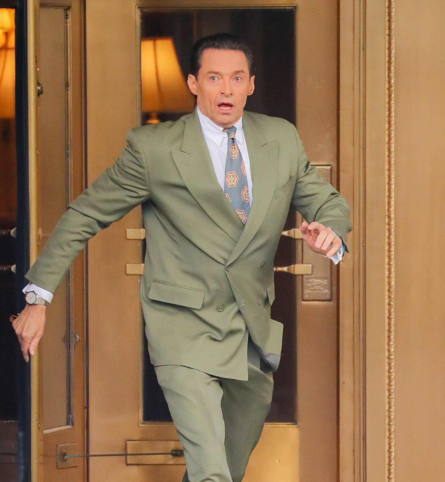 Hugh Jackman seen running out of a building door while filming 'Bad Education' in New York City