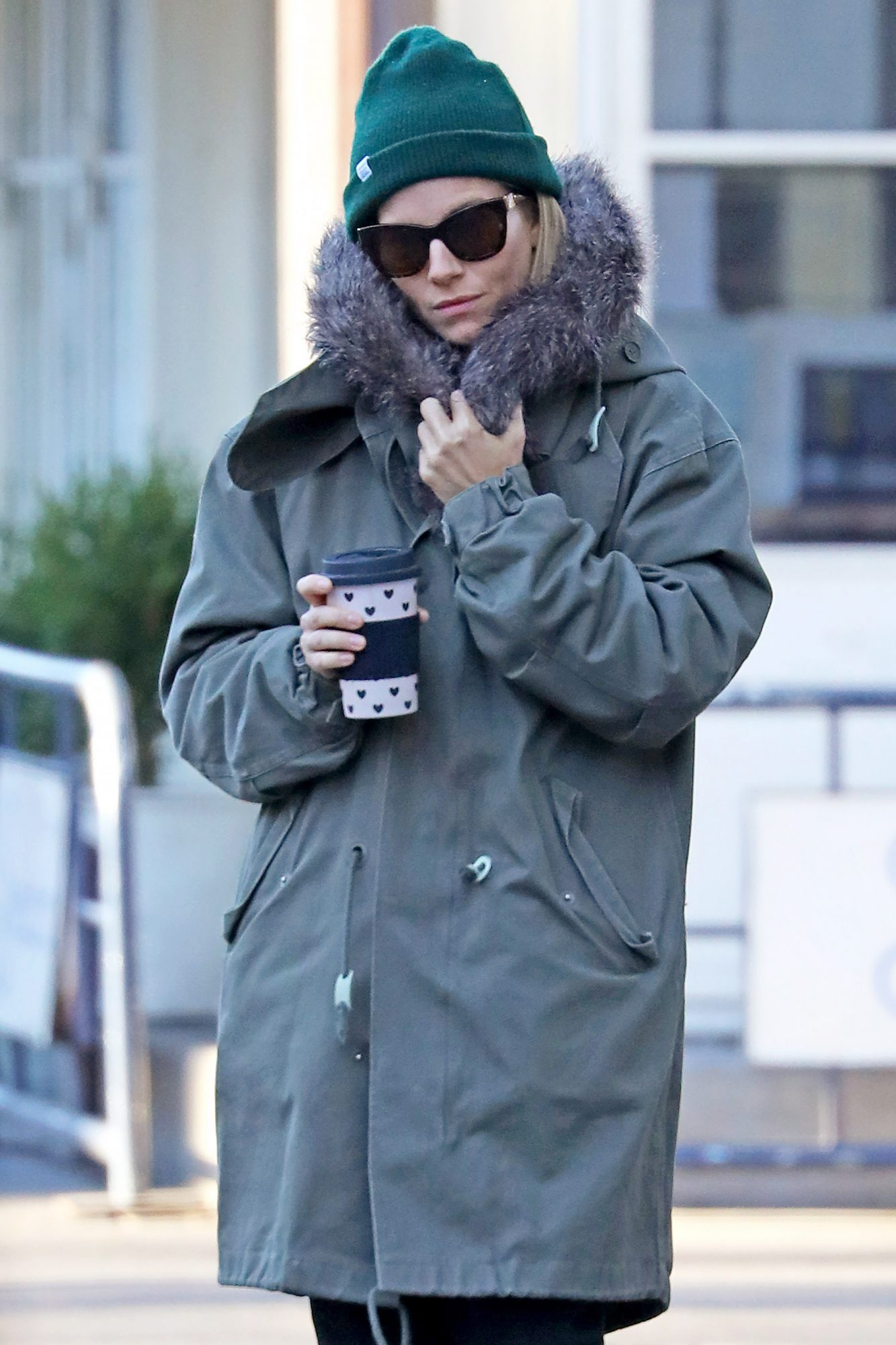 Sienna Miller keeps warm wearing a green Winter Jacket on her morning stroll, NYC
