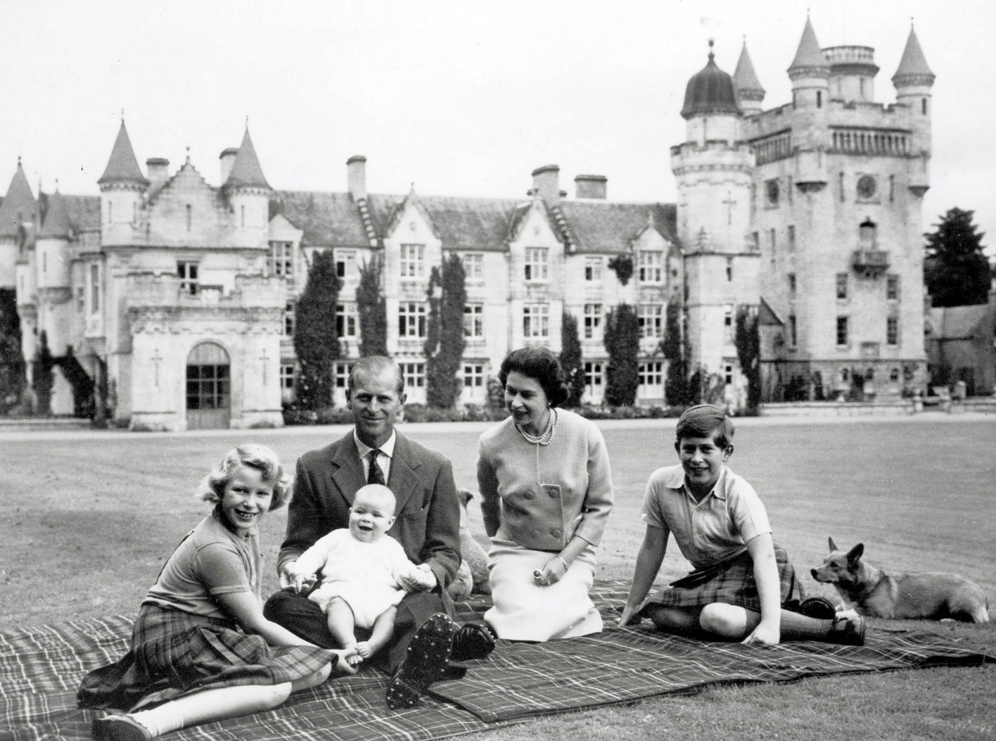 Royalty. 9th September 1960. During their holiday on the Balmoral Castle estate the Royal family sit together within the grounds, a happy smiling baby Prince Andrew held on his father the Duke of Edinburgh+s lap. Pictured also smiling is Queen Elizabeth I