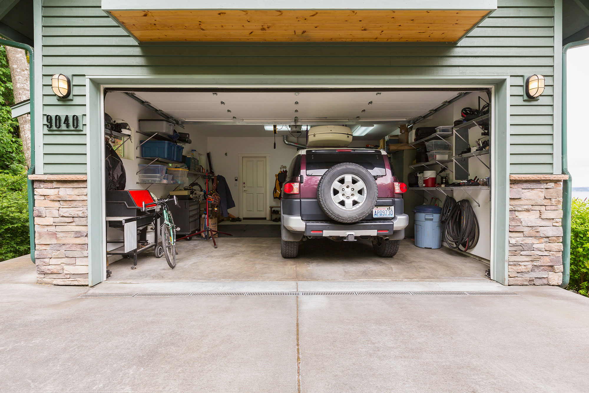 Open residential garage with car, bicycle and other possessions visible